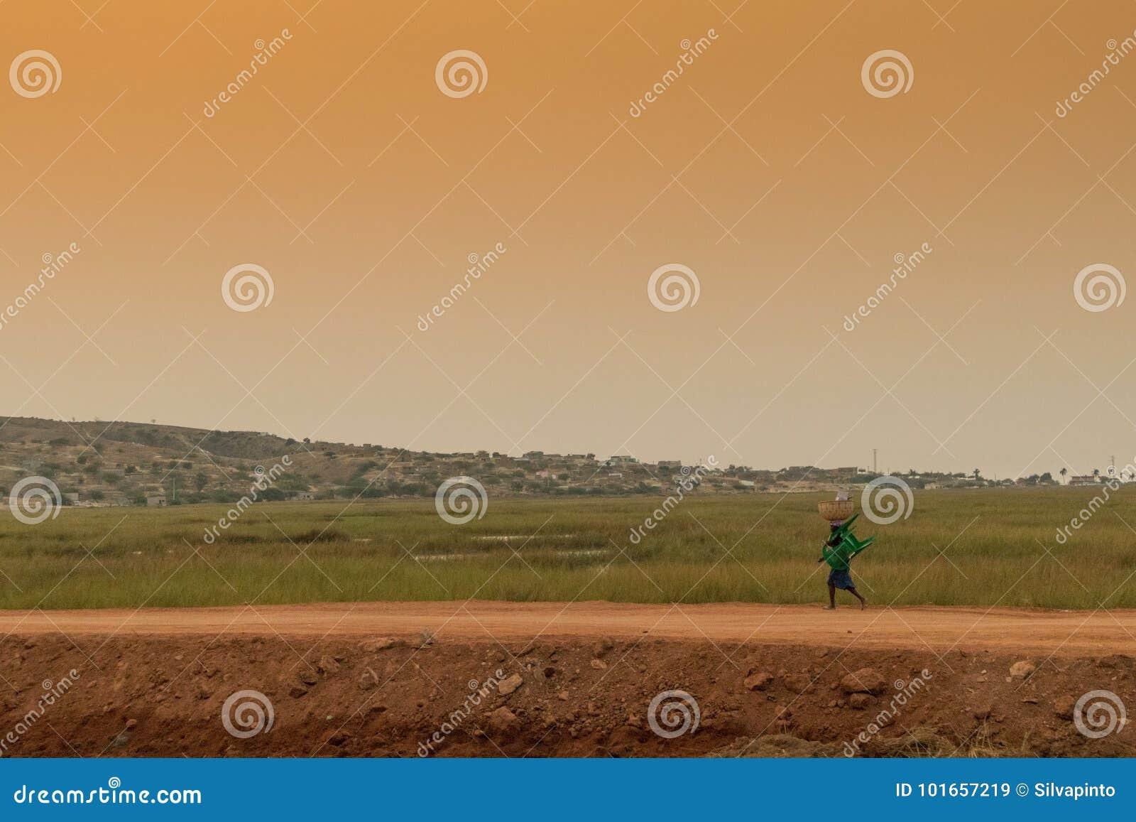 Gente rural africana que vuelve de trabajo, con puesta del sol Sumbe