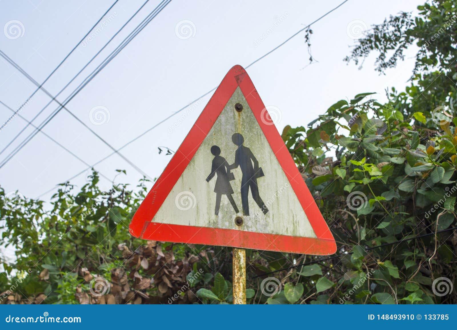 Gente triangolare di cautela del segnale stradale su un fondo dei cespugli verdi