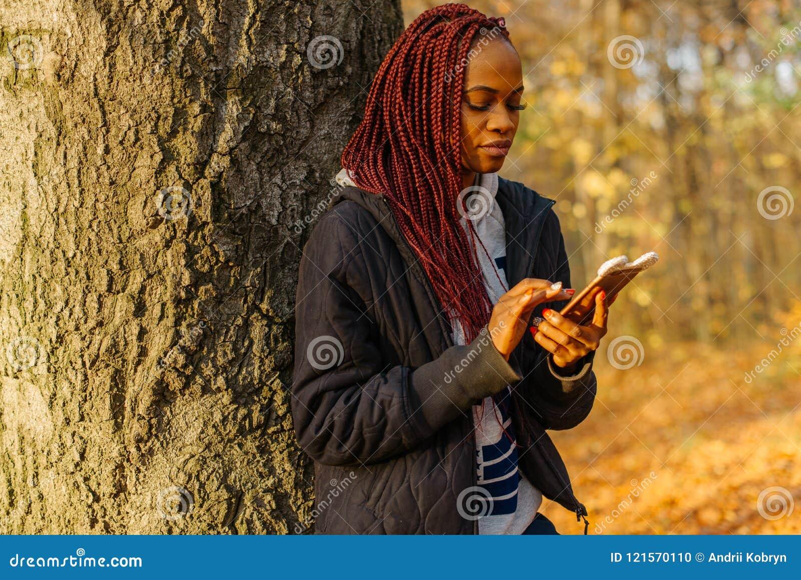 Gente y tecnología La mujer africana joven adorable con el pelo rojo es de charla y de ojeada en el teléfono móvil mientras que