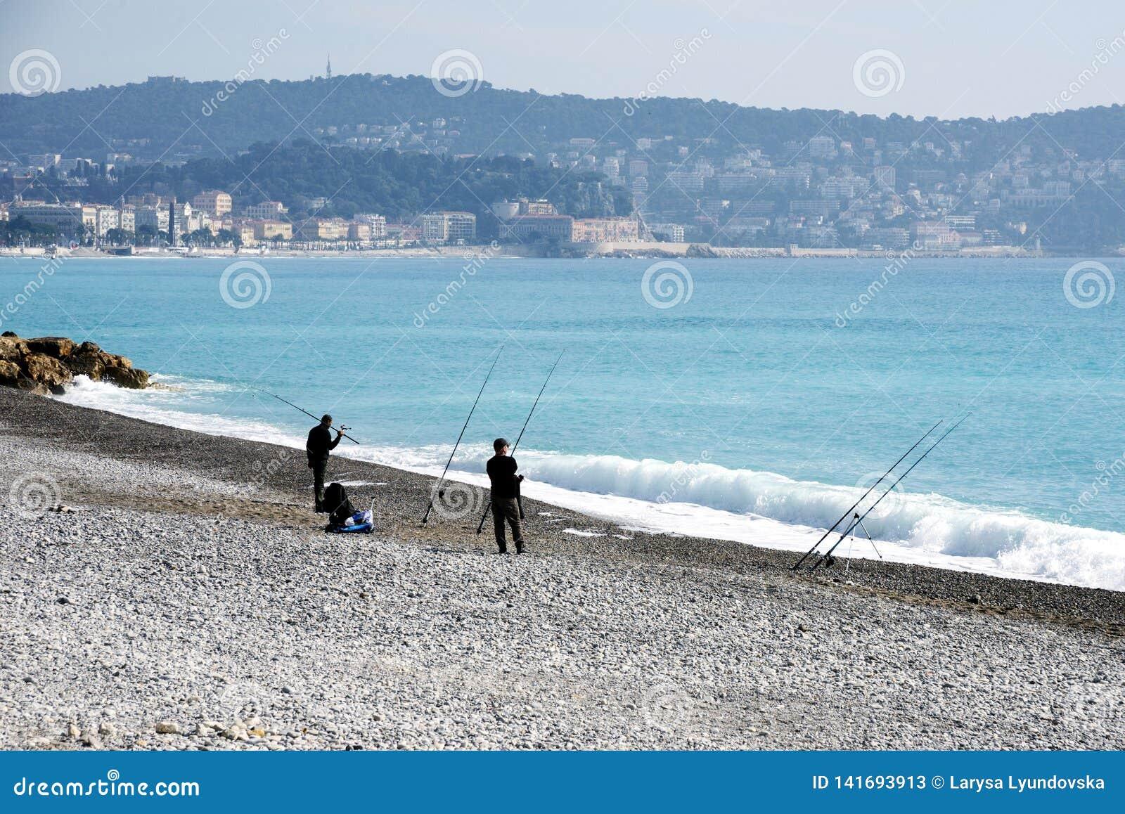 Gentil, France, mars 2019 Deux pêcheurs pêchant avec les cannes à pêche sur le Pebble Beach de Nice ` Azur de Cote D Le brouillar
