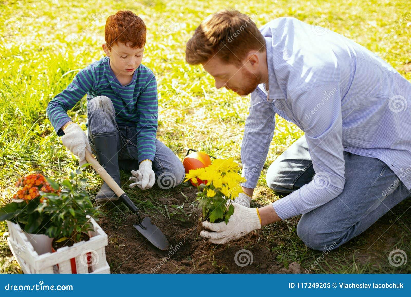 Gentil père et fils positifs travaillant ensemble