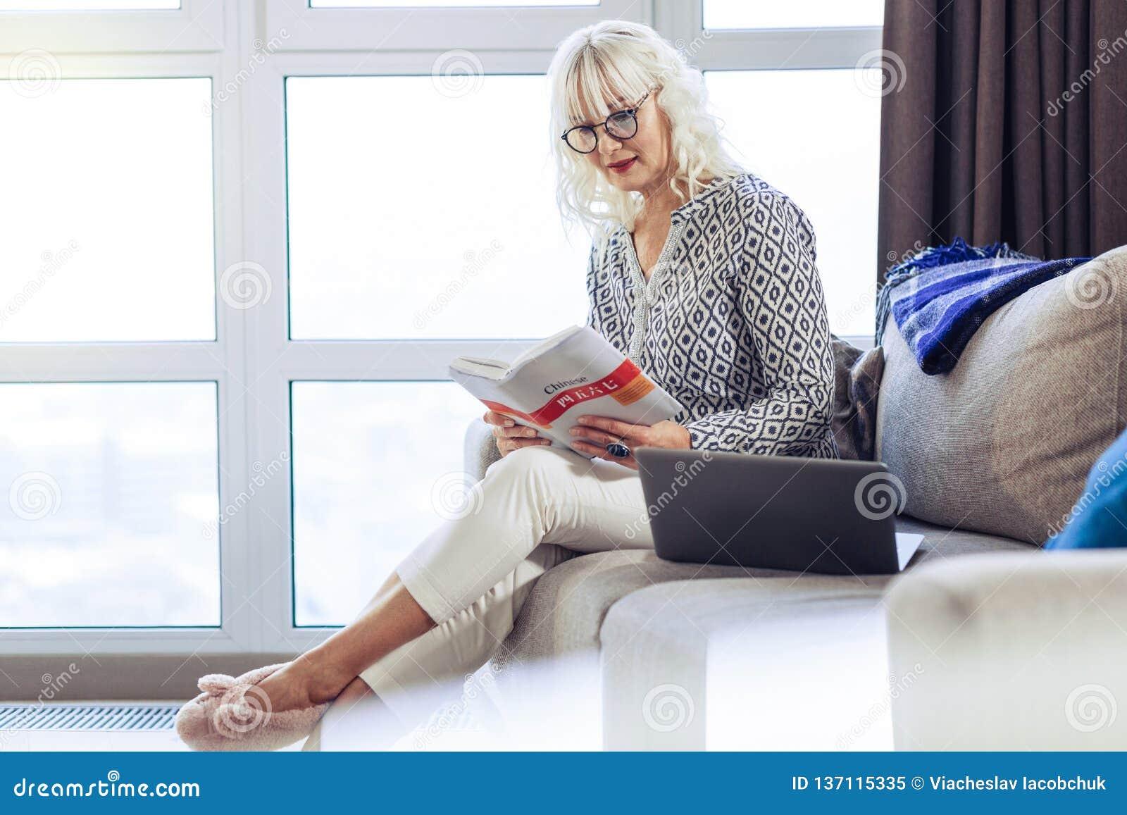 Gentille femme blonde lisant un livre intéressant