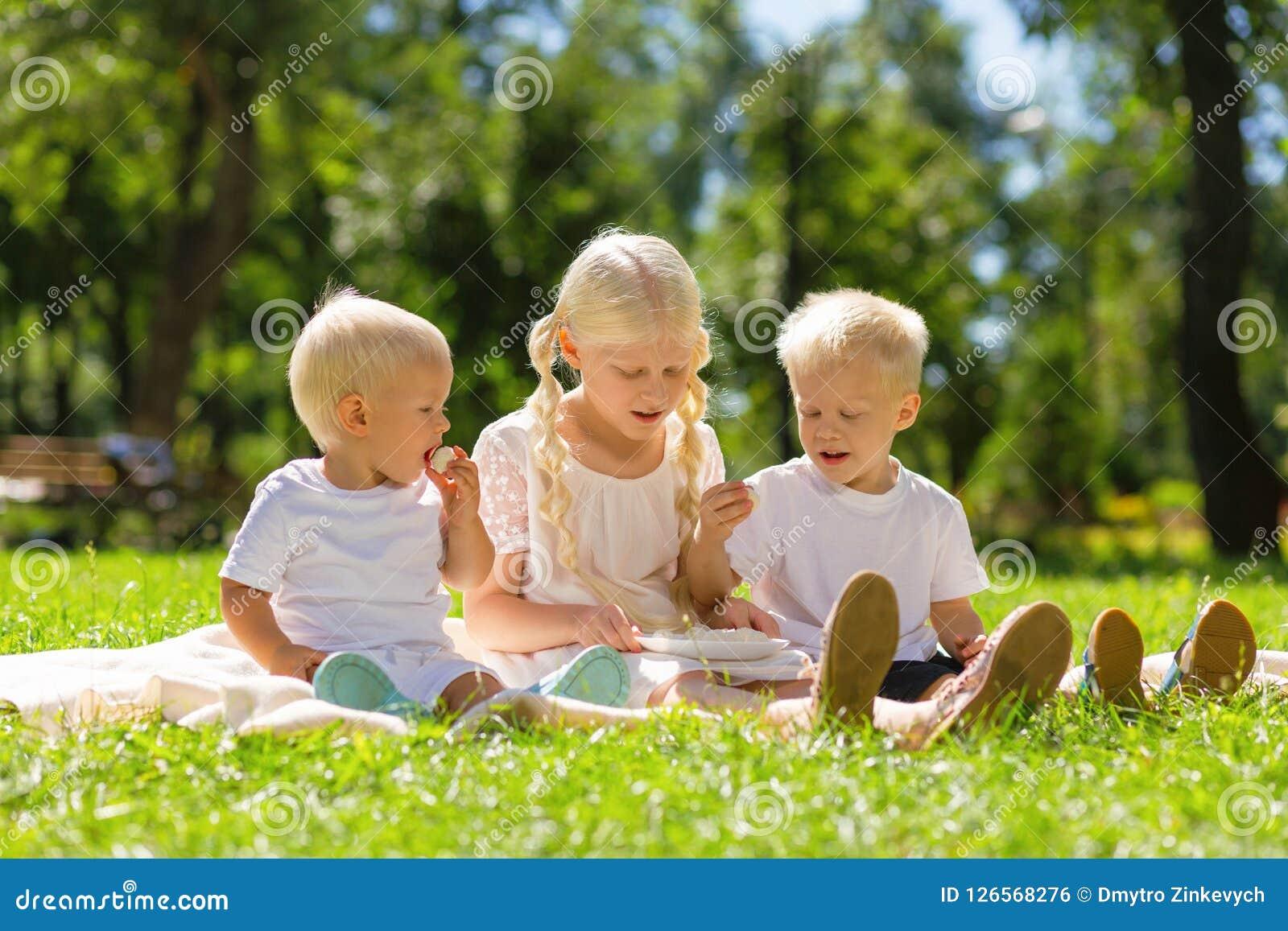 Gentille fille et garçons s asseyant en tout parc ensemble