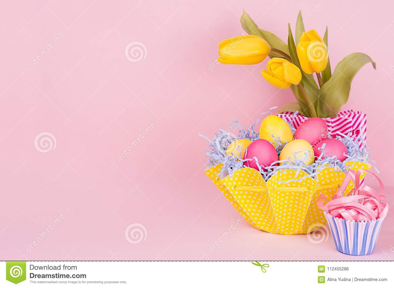 Gentle elegant soft pastel easter decoration - painted eggs, yellow tulips, cupcake on pink background, copy space.