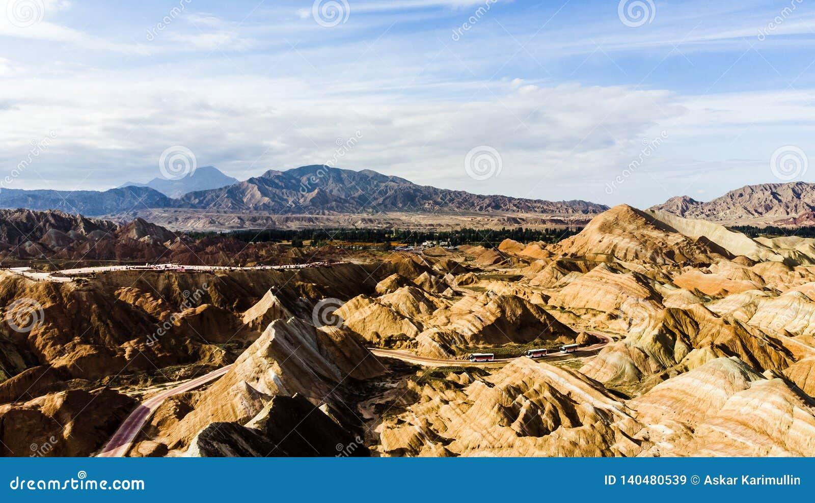 Geologiska regnbågeberg parkerar Turist- bussar på en väg i en dal på en Sunny Day
