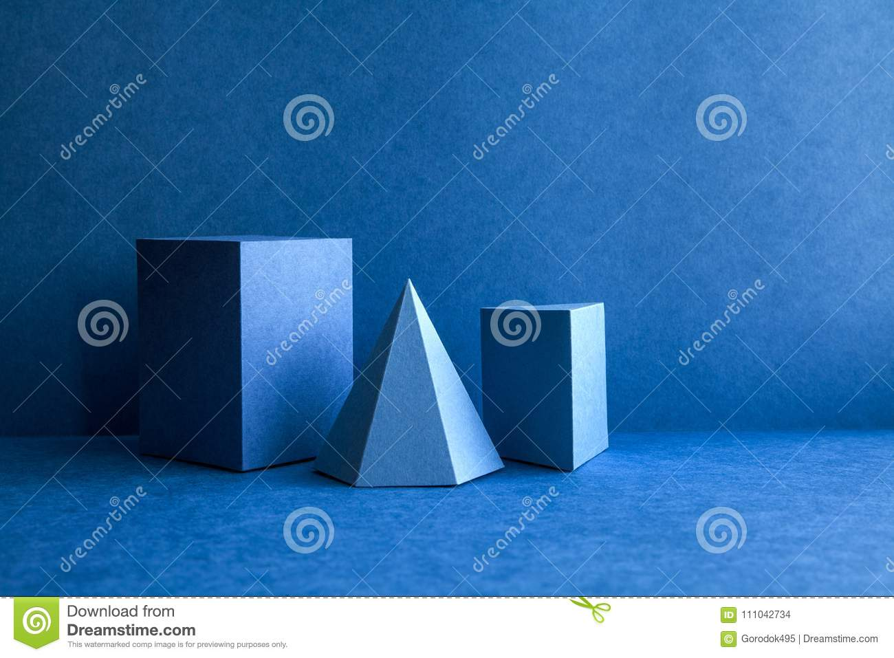 Geometrical figures still life composition. Three-dimensional prism pyramid tetrahedron rectangular cube objects on blue
