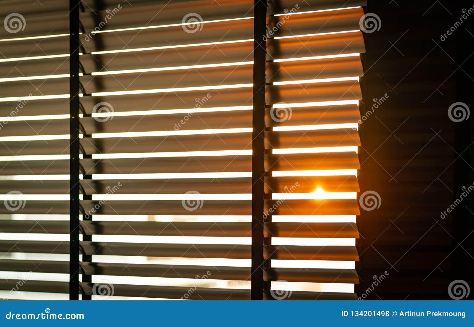 Geopende Venetiaanse plastic zonneblinden met zonlicht in de ochtend Wit plastic venster met zonneblinden Binnenlands ontwerp van