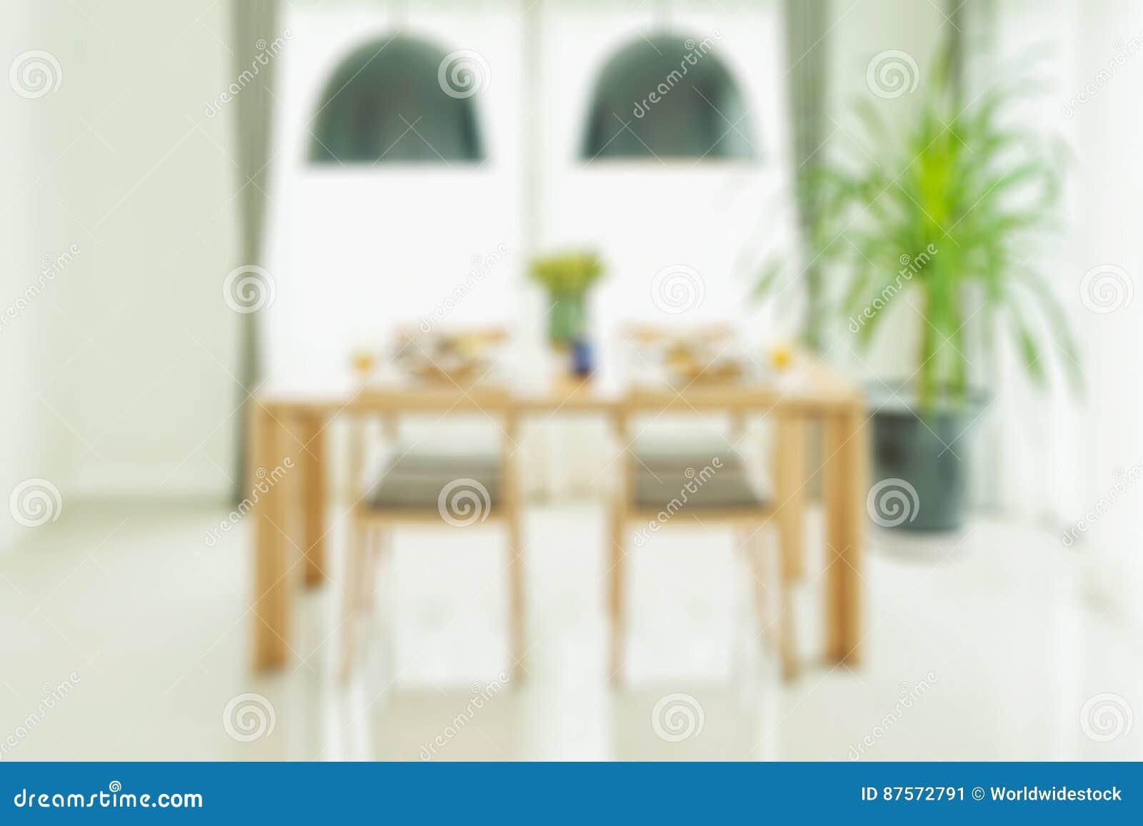 Geopende witte deur voor houten eettafel en stoelen met het