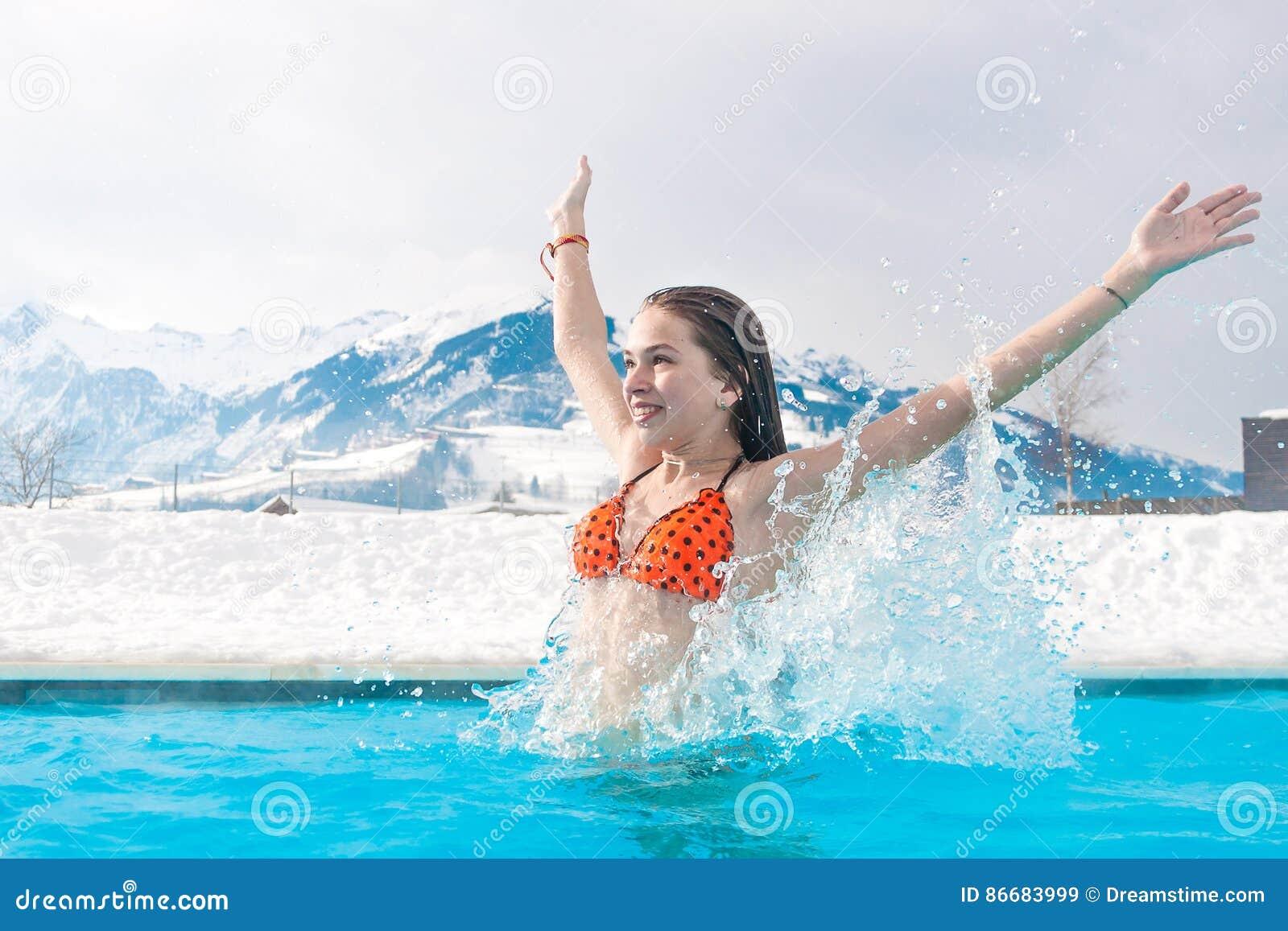 Geotermiczny zdrój Dziewczyna cieszy się dopłynięcie w błękitne wody na tle śnieżne góry