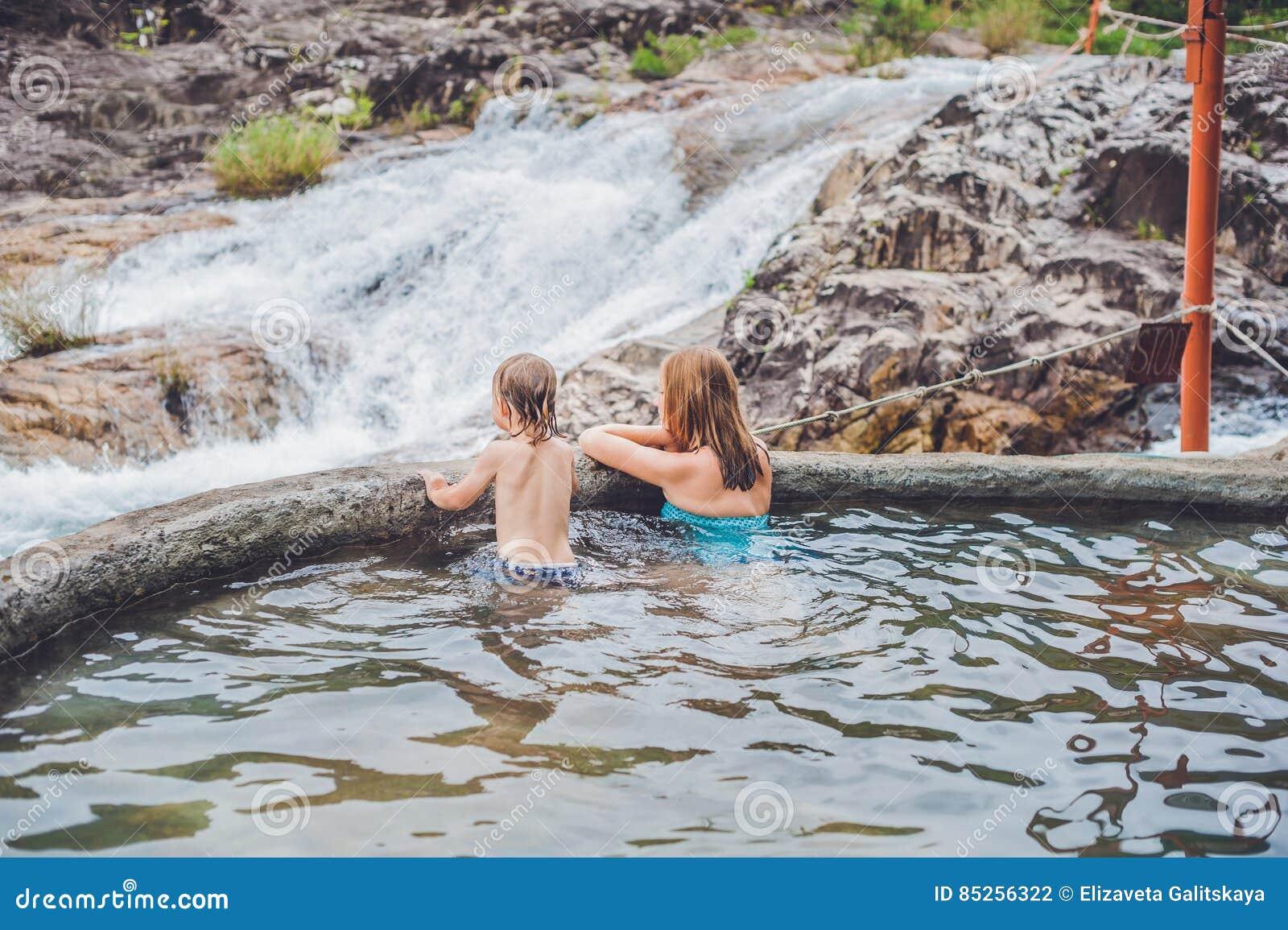 Geotermiczny zdrój Matka i syn relaksuje w gorącej wiosny basenie przeciw tłu siklawa