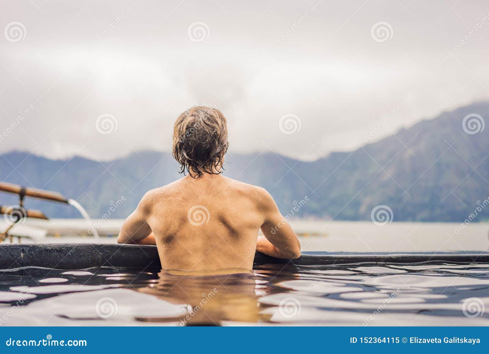 Geothermal Spa mens het ontspannen in hete de lentepool Jonge mens die van baden genieten ontspannen in een blauwe waterlagune, t