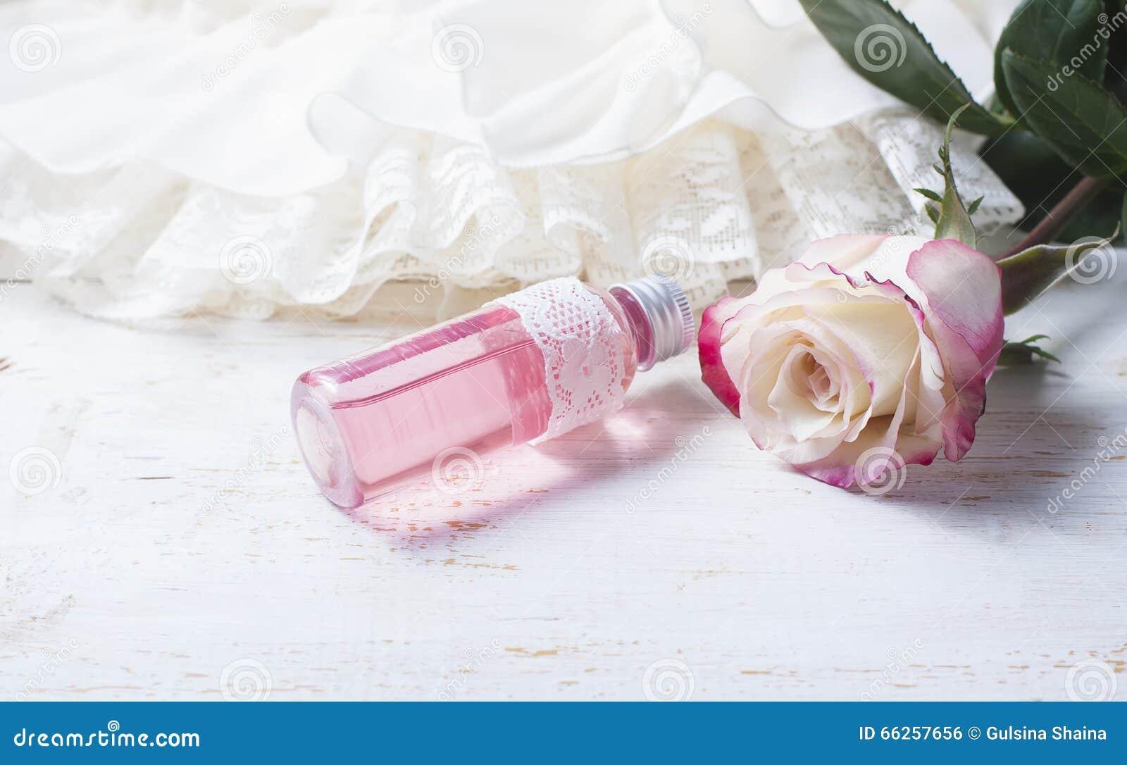 Geparfumeerd rozewater in een fles op een houten lijst