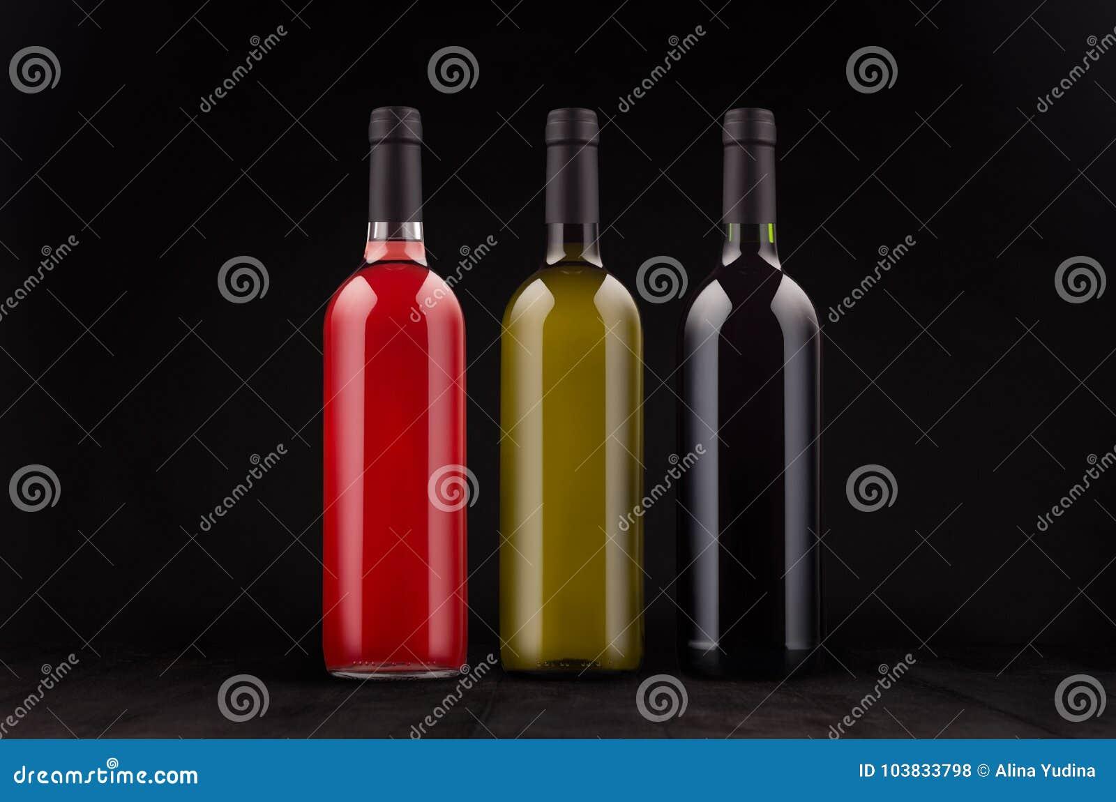 Geplaatste wijn de flessen - rood, groen, nam toe - bespotten omhoog op elegante donkere zwarte houten achtergrond