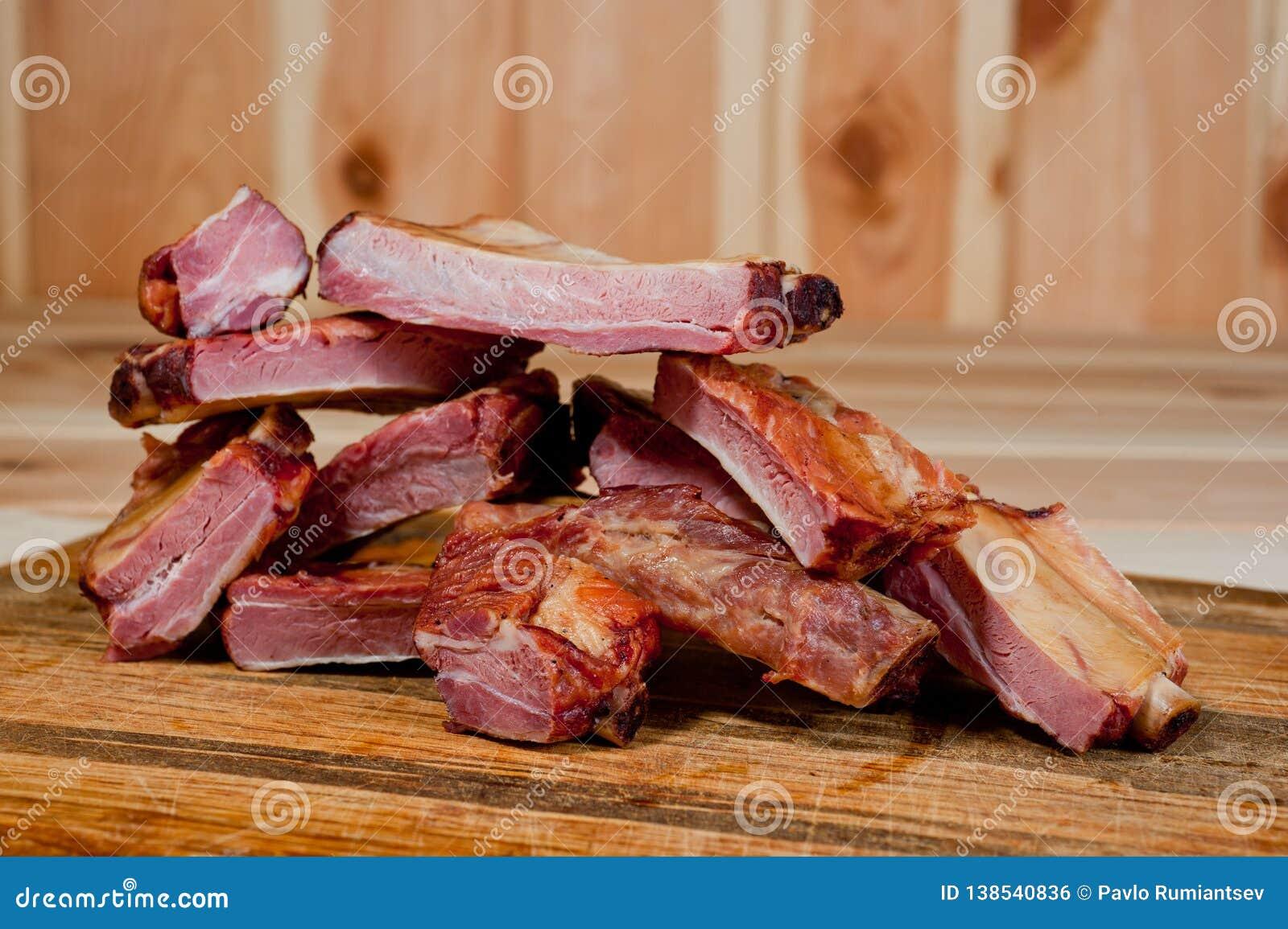 Geräucherte Schweinefleischrippen saftig und fleischig auf einem hölzernen Schneidebrett