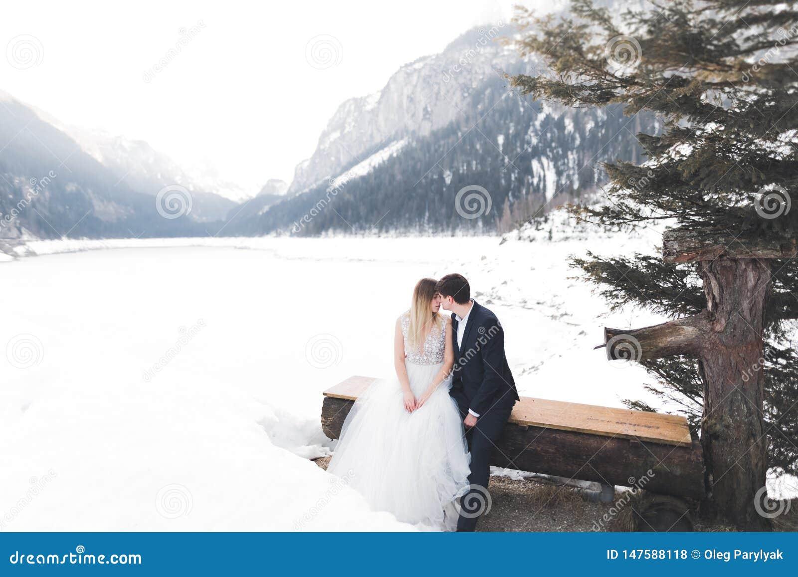 Gerade das k?ssende verheiratete Paar, Berge gestalten im Schnee auf dem Hintergrund landschaftlich
