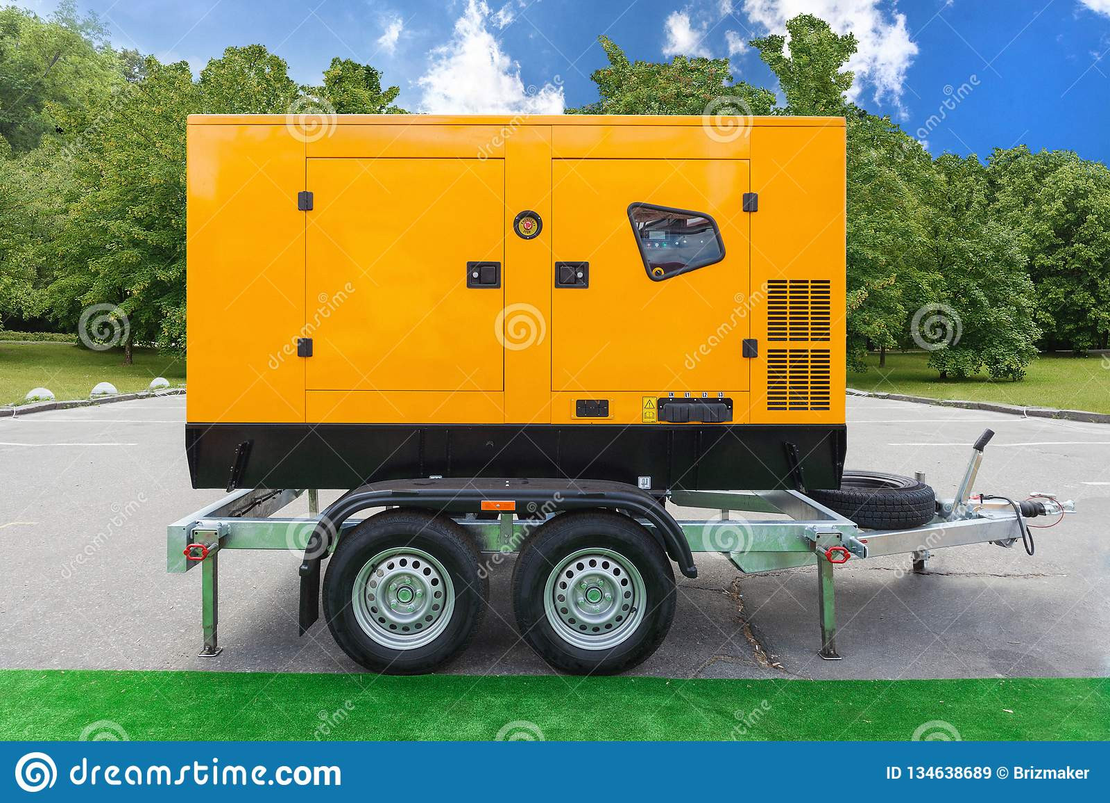 Gerador diesel móvel da carga para a energia elétrica da emergência que está exterior contra árvores verdes e o céu azul