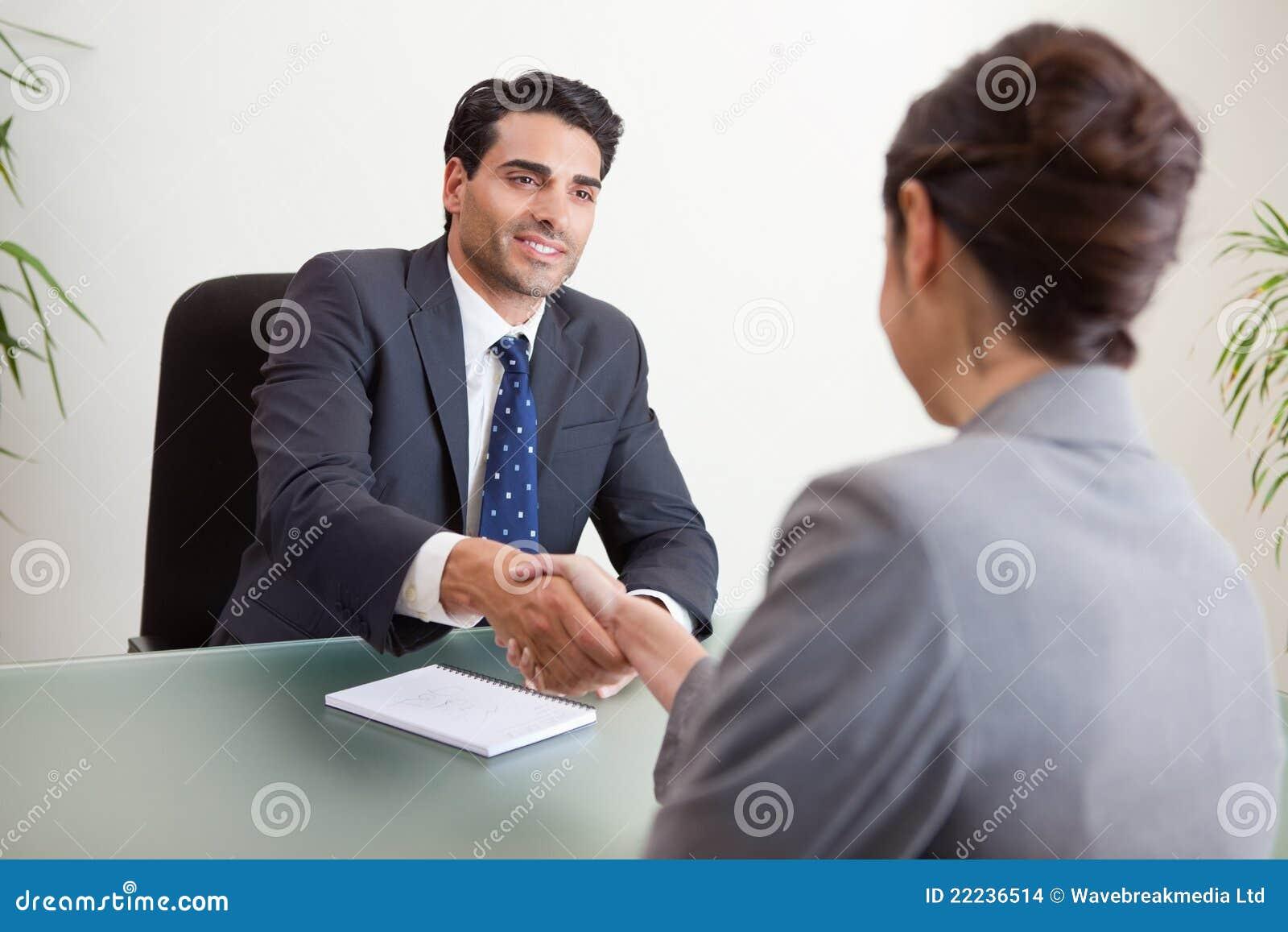 Gerente de sorriso que entrevista um candidato fêmea