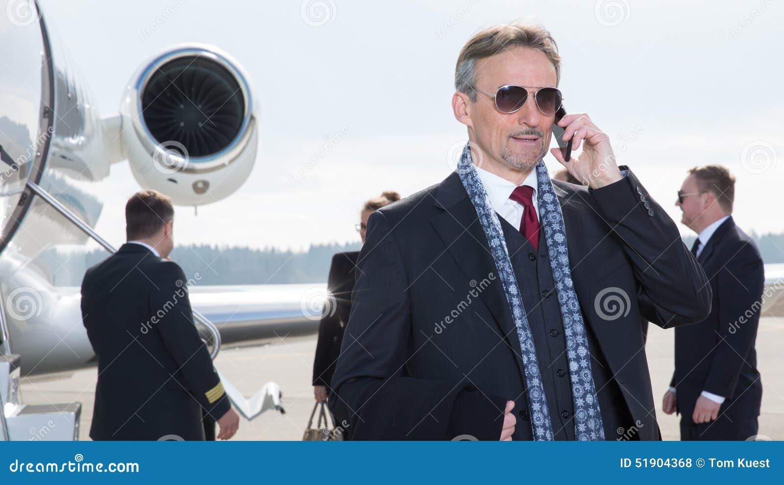 Gerente executivo na frente do jato incorporado usando um smartphone