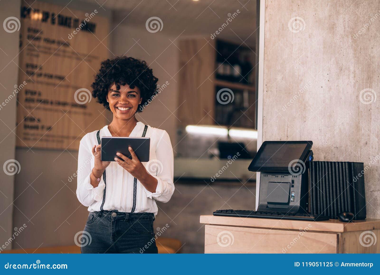Gerente fêmea do restaurante com uma tabuleta digital