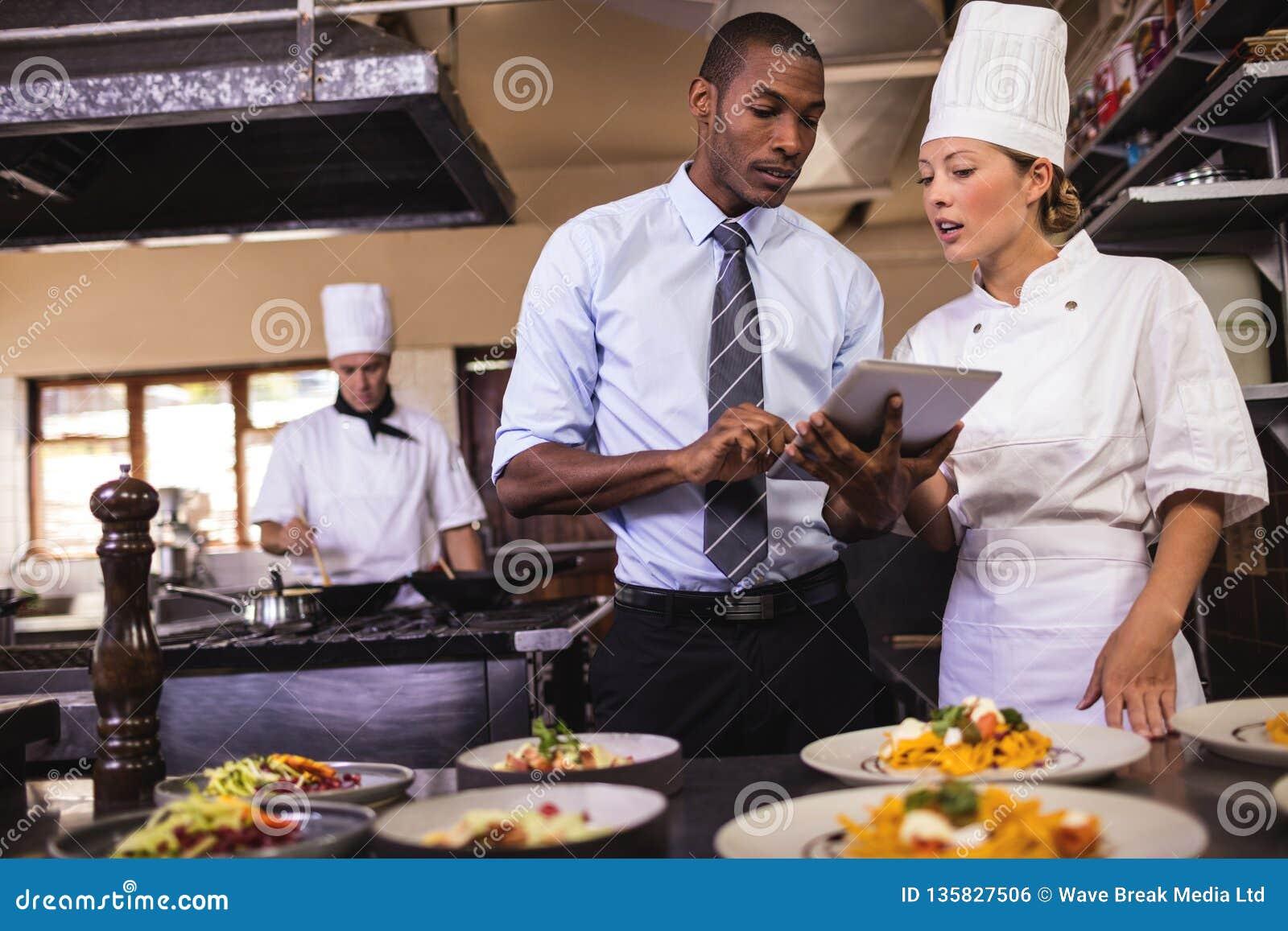 Gerente masculino e cozinheiro chefe fêmea que usa a tabuleta digital na cozinha