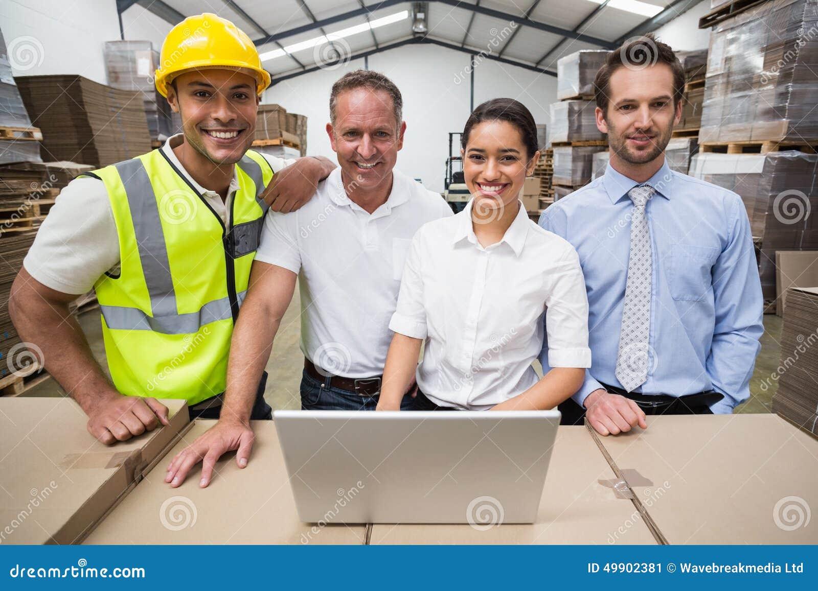 Gerentes e trabalhador do armazém que sorriem na câmera