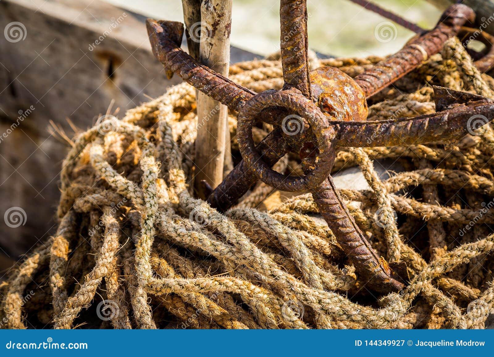 Geroest anker met versleten kabels op strand in Zanzibar