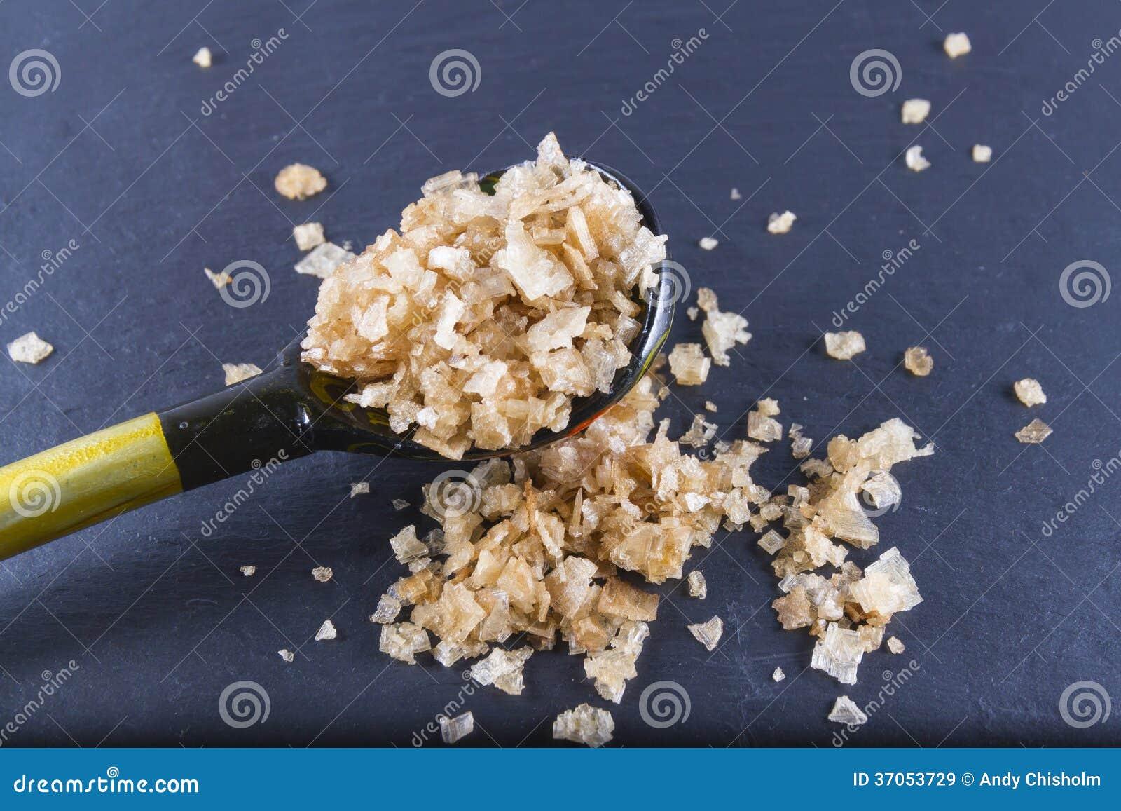 Gerookte overzeese zoute vlokken, op een houten lepel en verspreid. Macro.