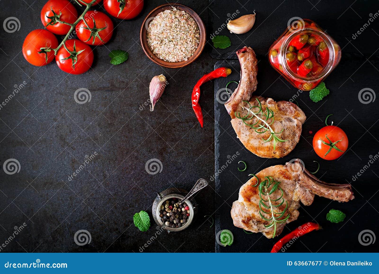 Geroosterd sappig lapje vlees op het been met groenten op een donkere achtergrond