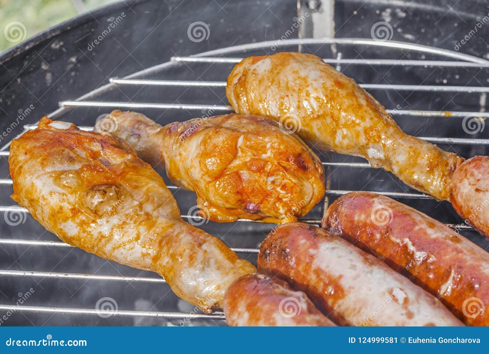 Geroosterd worsten en van kippenbenen close-up op de grill