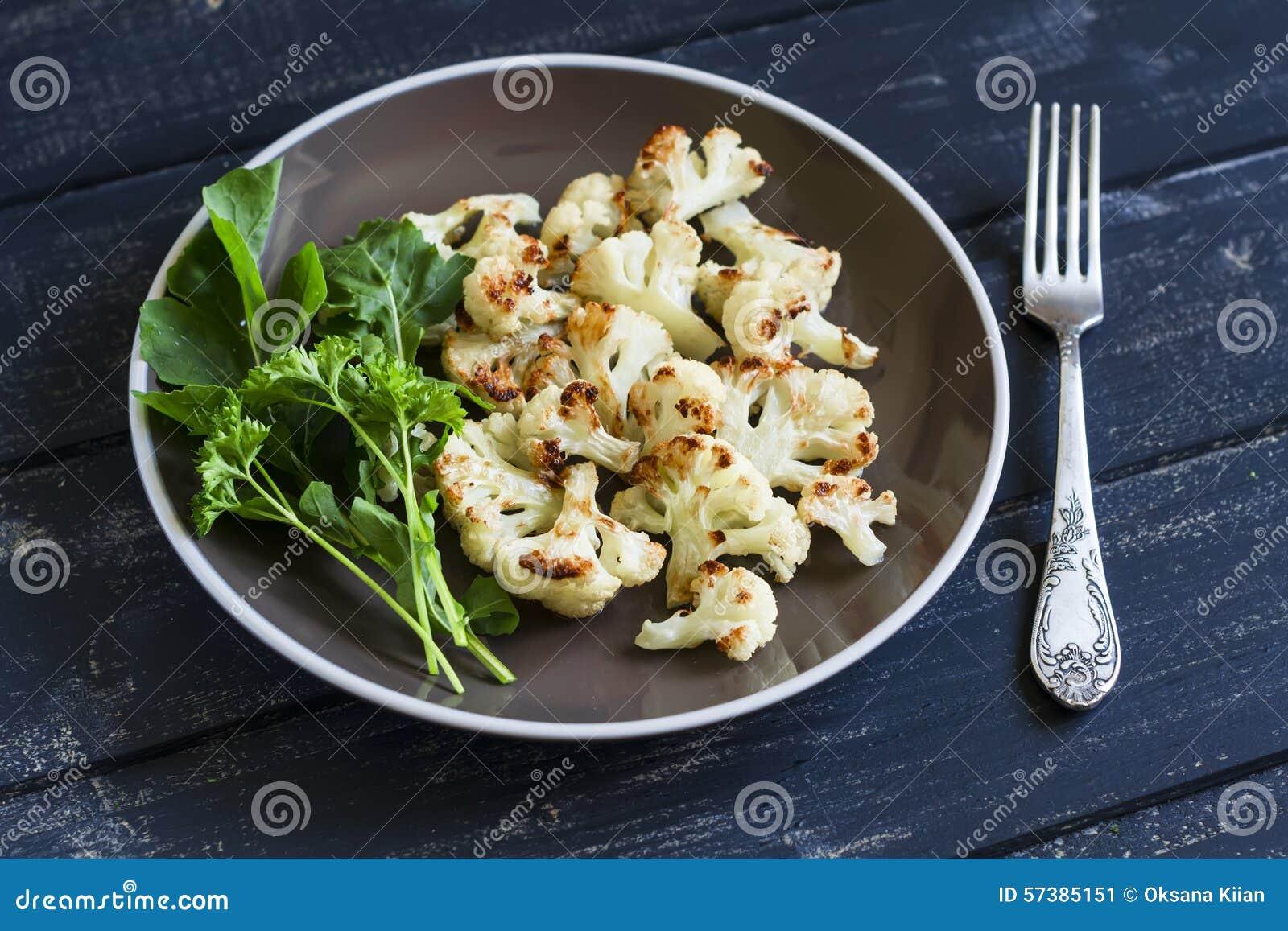 Geroosterde bloemkool en verse groene salade op een bruine plaat