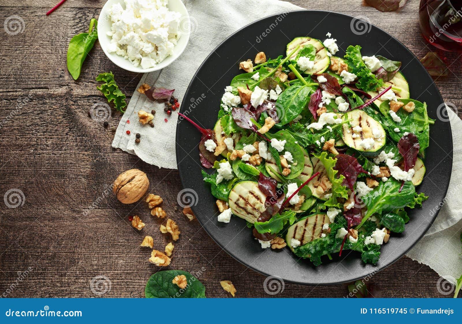 Geroosterde Courgettesalade met feta-kaas, okkernootnoten en glas rode wijn in een zwarte plaat op houten lijst