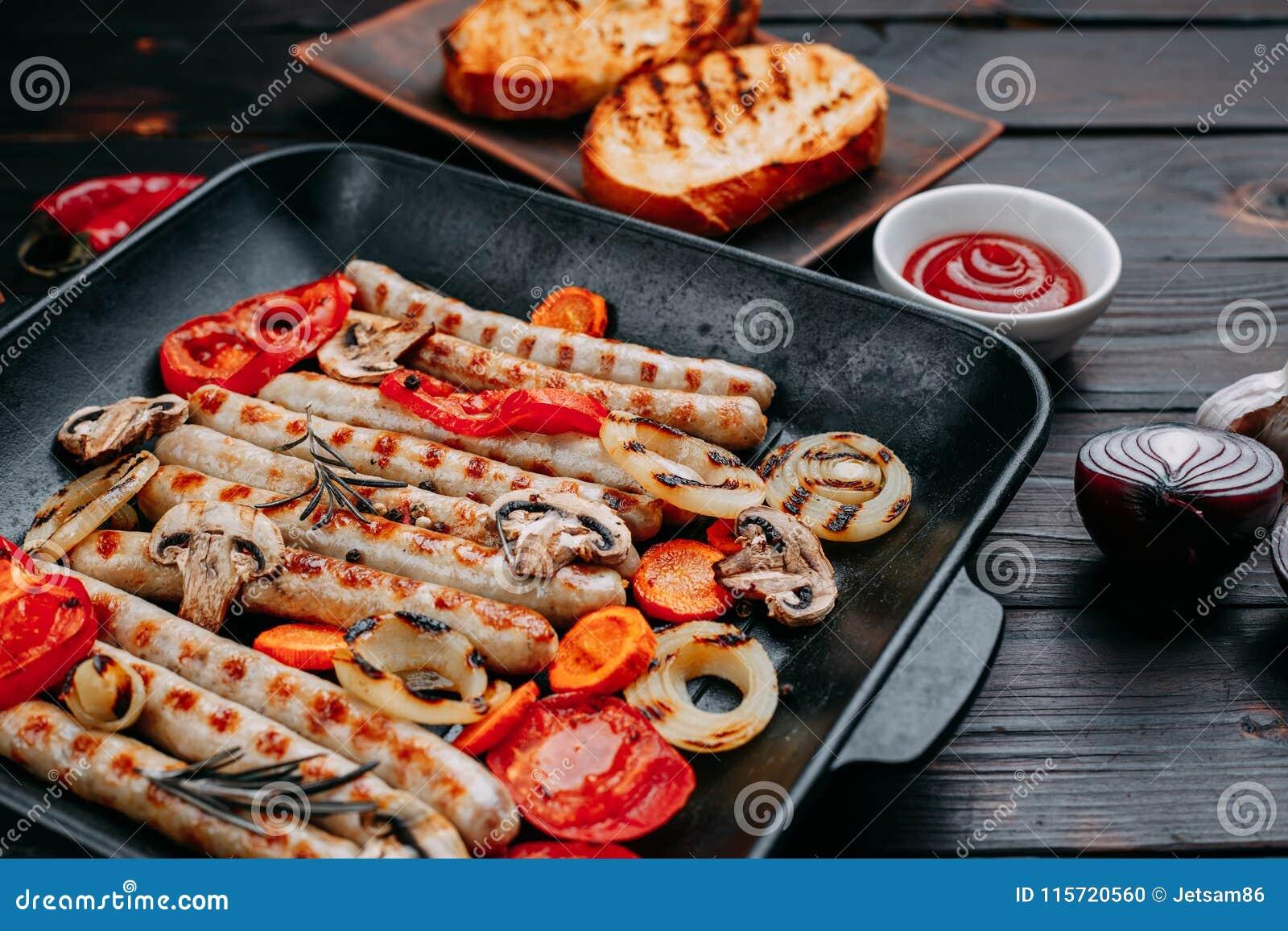 Geroosterde die worsten en groenten in een grillpan worden gediend met saus