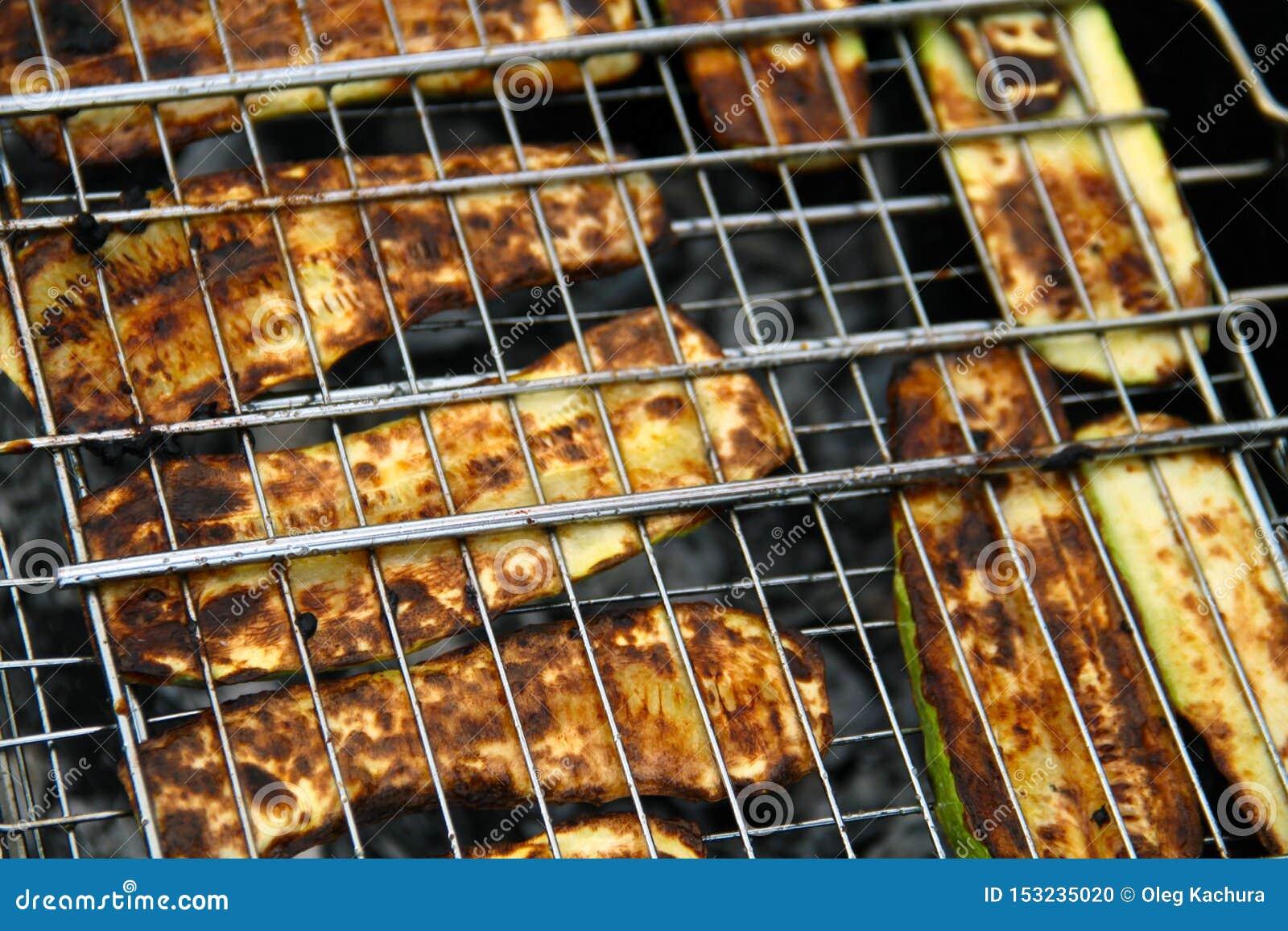 Geroosterde gesneden courgette op een brand die in rijen op de grill onder brandende steenkolen wordt opgemaakt