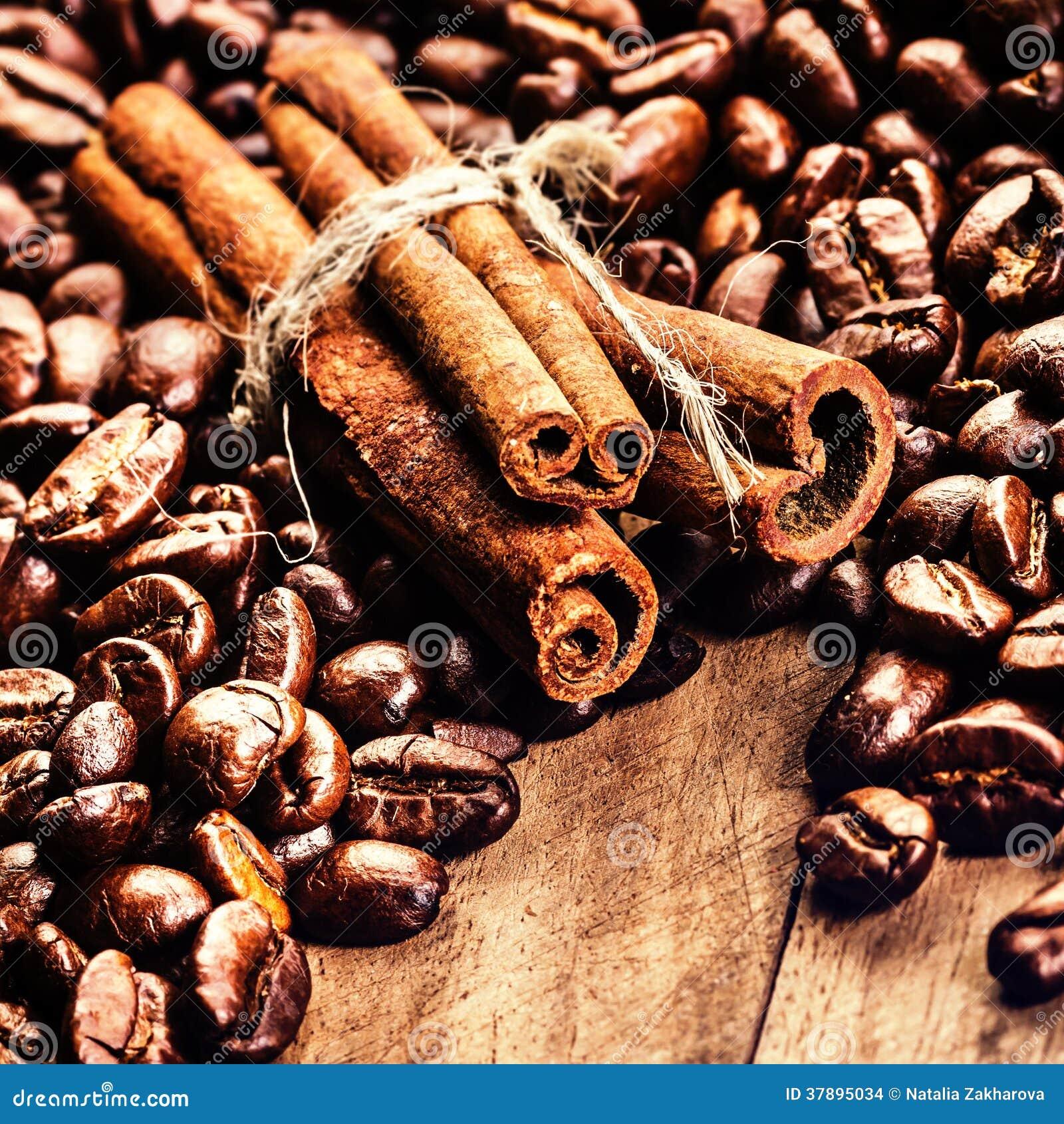 Geroosterde Koffiebonen en pijpjes kaneel op grunge houten backgr