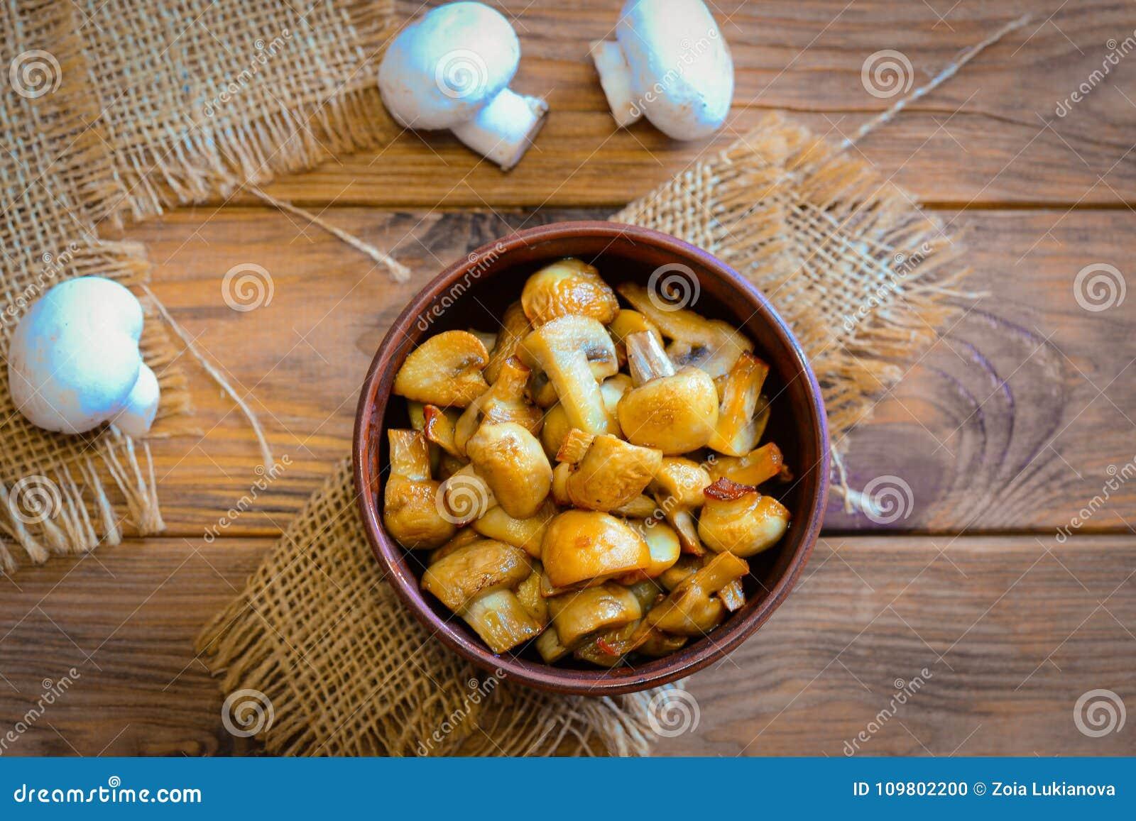 Geroosterde Paddestoelen Eigengemaakte geroosterde paddestoelen in een kom op een houten achtergrond Vegetarisch low-calorie dine