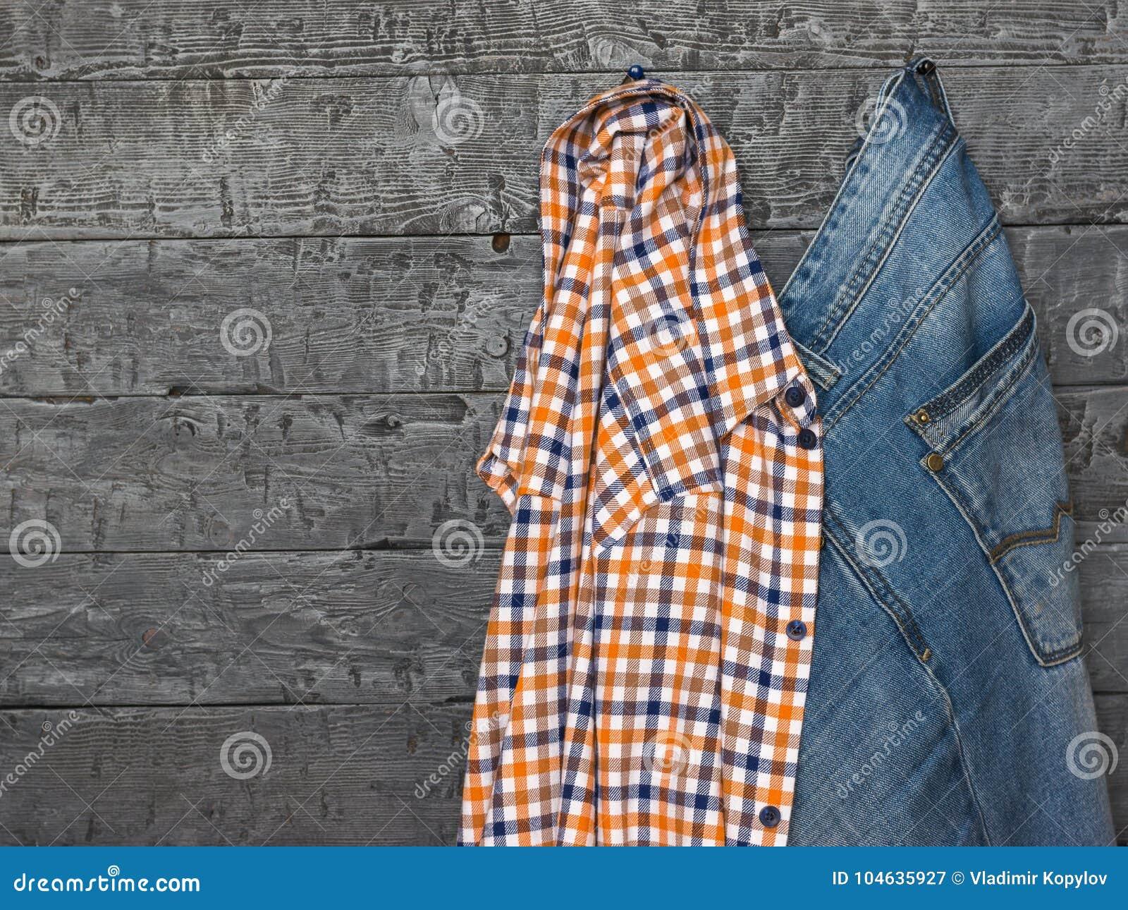Download Geruite Overhemd En Jeans Op Uitstekende Houten Muur Stock Afbeelding - Afbeelding bestaande uit samenvatting, zaken: 104635927