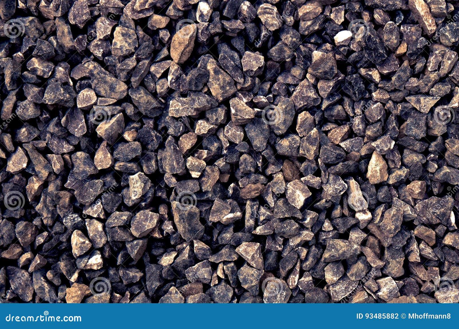 Gesamtheit von den dunklen groben grauen Steinen, die an einer Steingrube zerquetscht werden - bestreuen Sie Muster mit Kies