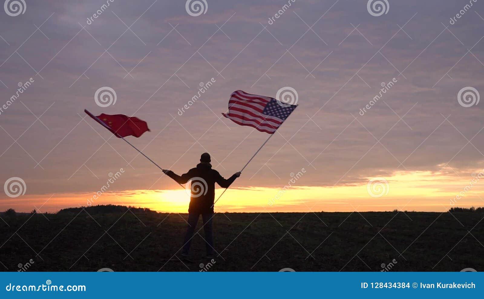 Gesamtlänge von den amerikanischen und chinesischen Flaggen, die im Wind durchbrennen wellenartig bewegende Flaggen in einer Land stock video