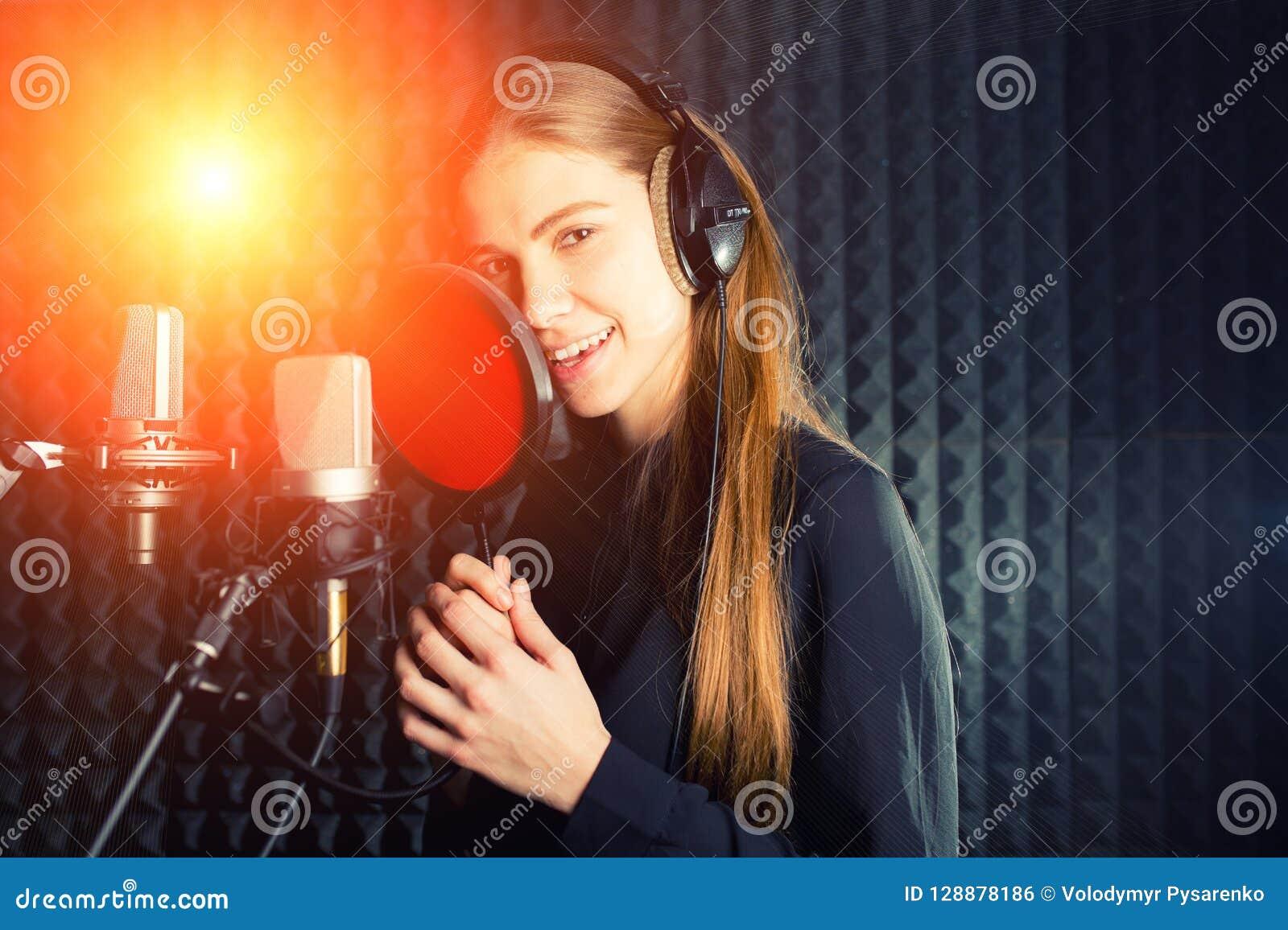 Gesangmädchen singen zum Berufsmikrofon im Rekordstudio Prozess von schaffen ein neues Schlaglied durch jungen Sänger