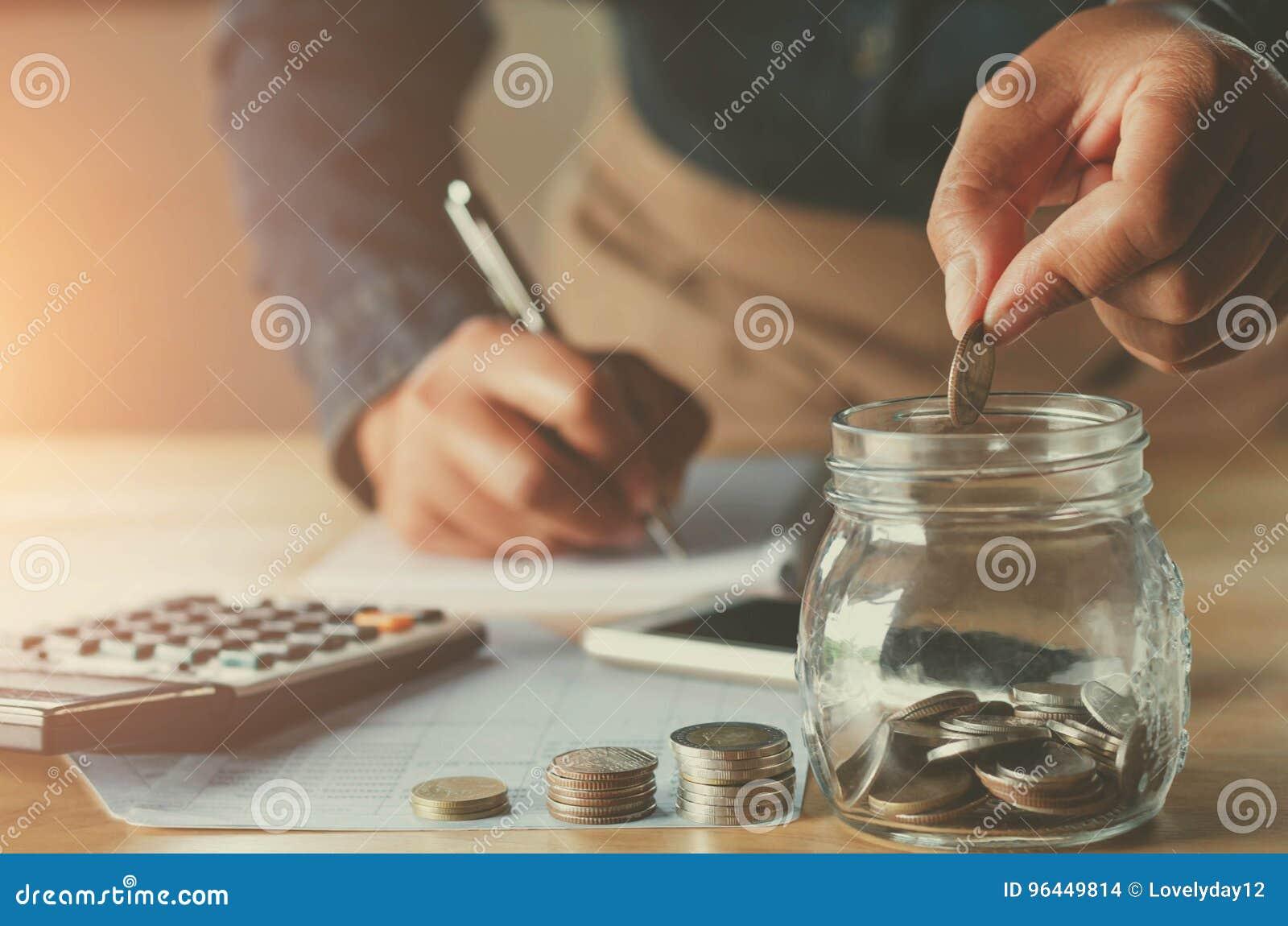 Geschäft accountin mit Einsparungsgeld mit der Hand, die herein Münzen setzt