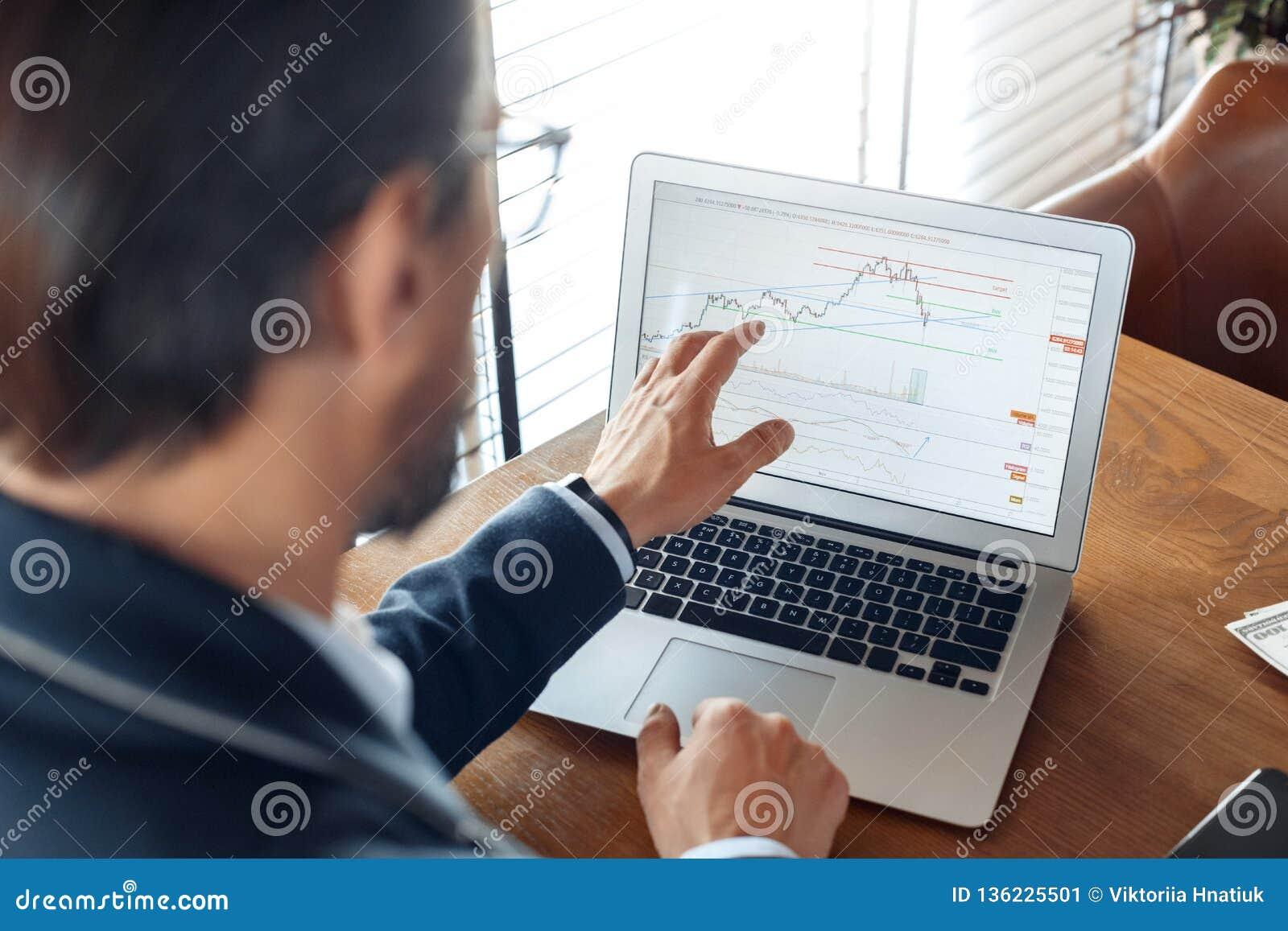 Geschäfts-Lebensstil Händler, der am Café betrachtet Handelsdiagramme auf Laptop starker hinterer Ansichtnahaufnahme sitzt