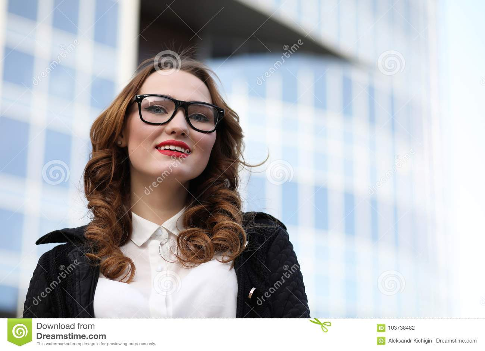 Geschäftsdame in der strengen Kleidung auf dem Hintergrund von Gebäuden