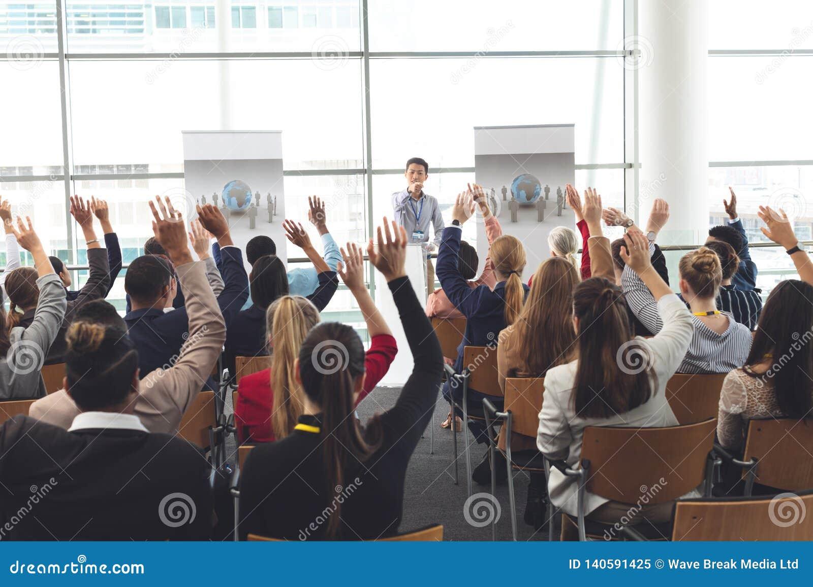 Geschäftsfachleute, die Hände in einem Geschäftsseminar anheben