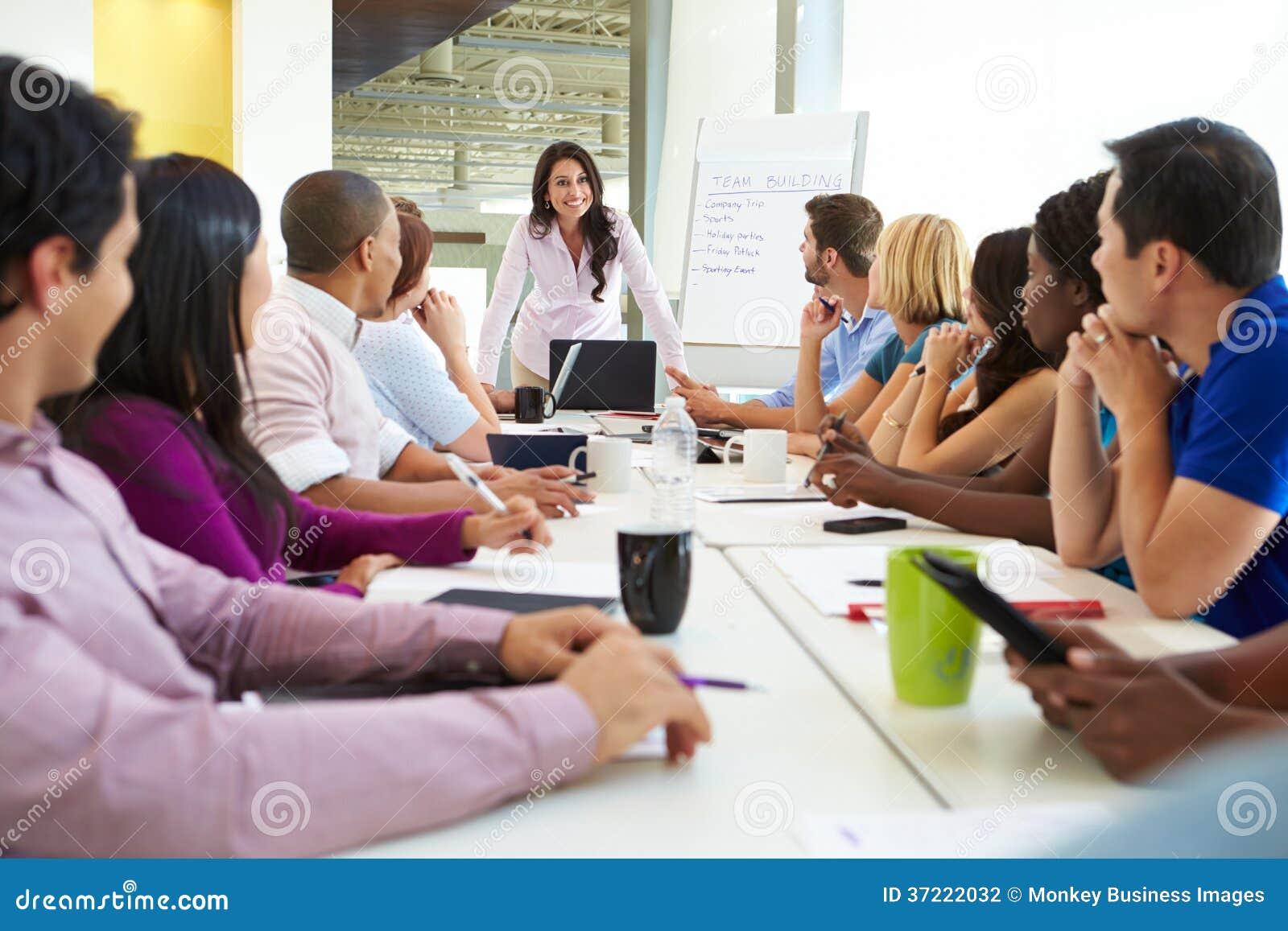 Geschäftsfrau-Addressing Meeting Around-Sitzungssaal-Tabelle