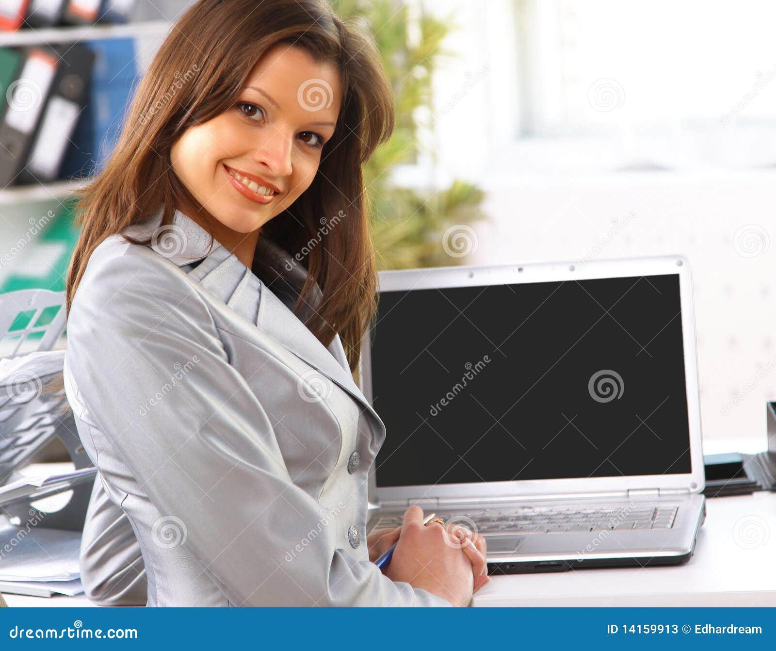 Geschäftsfrau, die den unbelegten Laptopbildschirm betriebsbereit zeigt
