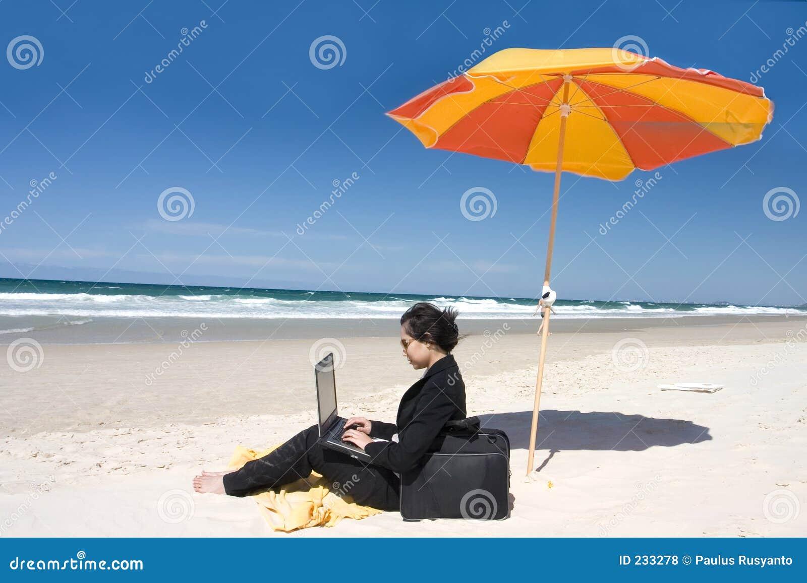 Geschäftsfrau, die am Strand arbeitet