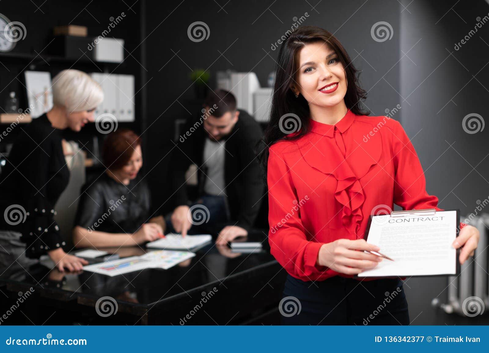 Geschäftsfrau mit Stift und Vertrag auf Hintergrund von Büroangestellten das Projekt besprechen