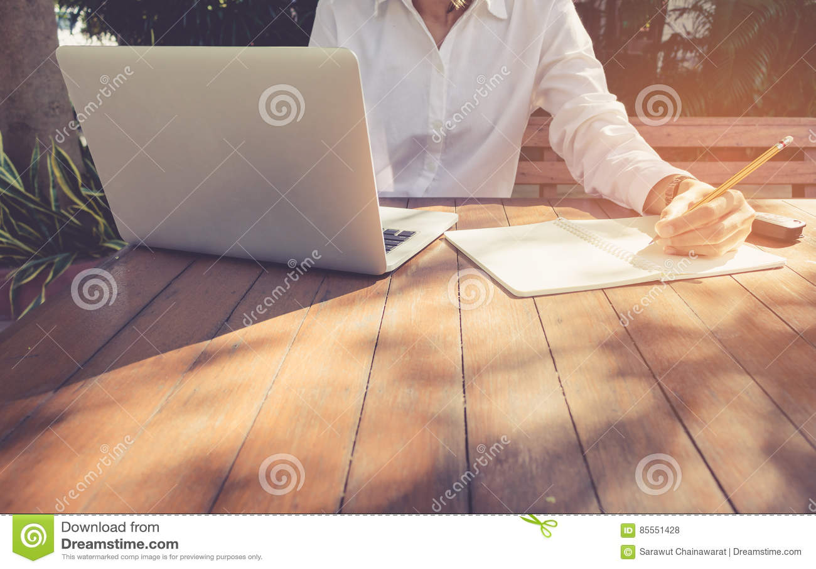Geschäftsfrau schreiben auf Notizbuch und verwenden das Laptoparbeiten im Freien im Kaffeestubeweinleseton