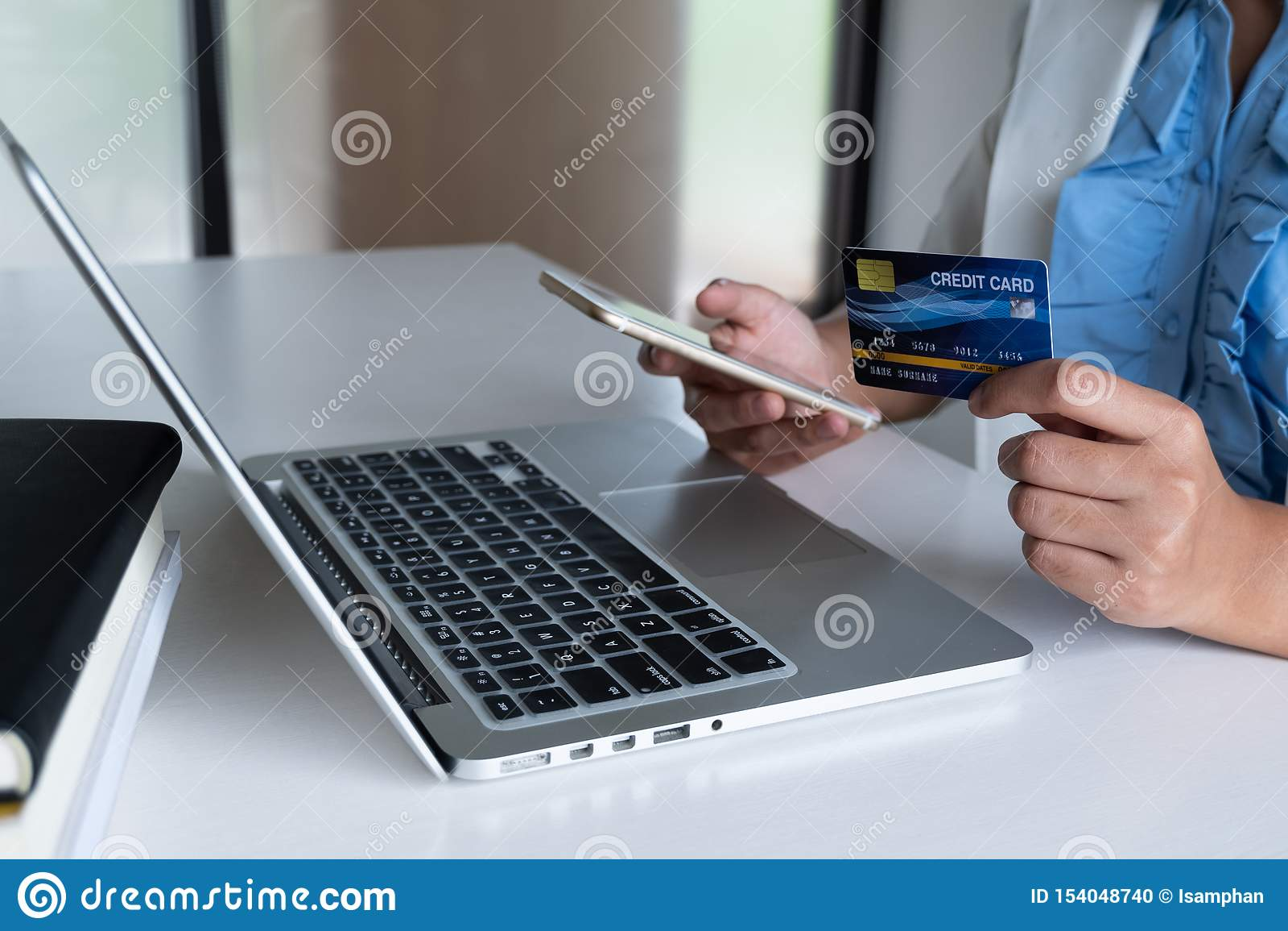 Geschäftsfrau-Verbrauchergebrauchskreditkarte für das on-line-Einkaufen an ihrem Laptop und an Telefon und eine Kaufzahlung im In