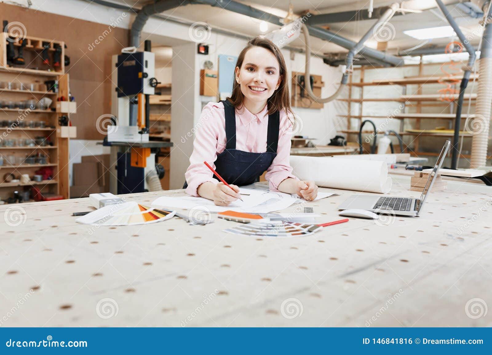 Geschäftsfrautischler, der an Laptop auf Holzoberfläche unter Bauwerkzeugen arbeitet Ist in der Nähe Smartphone, Laptop, Klemmbre